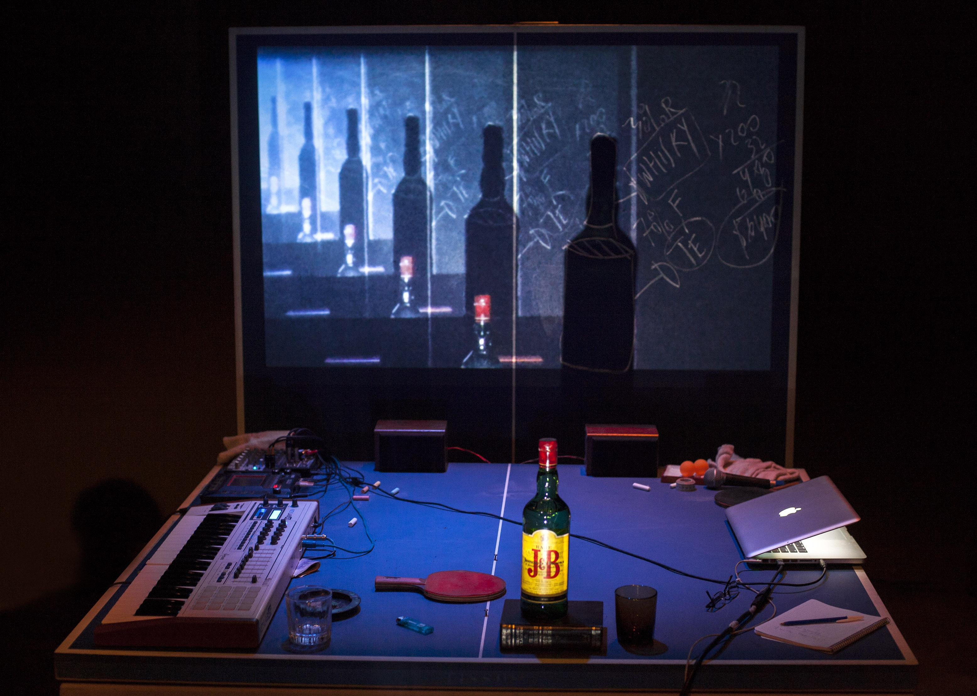 A ping-pong table is littered with a laptop, a musical keyboard, a bottle of whisky, glasses, cables, pens, and paper. The rear half of the table is vertical, showing a projected image of the bottle and its shadow that repeats and recedes into the distance.