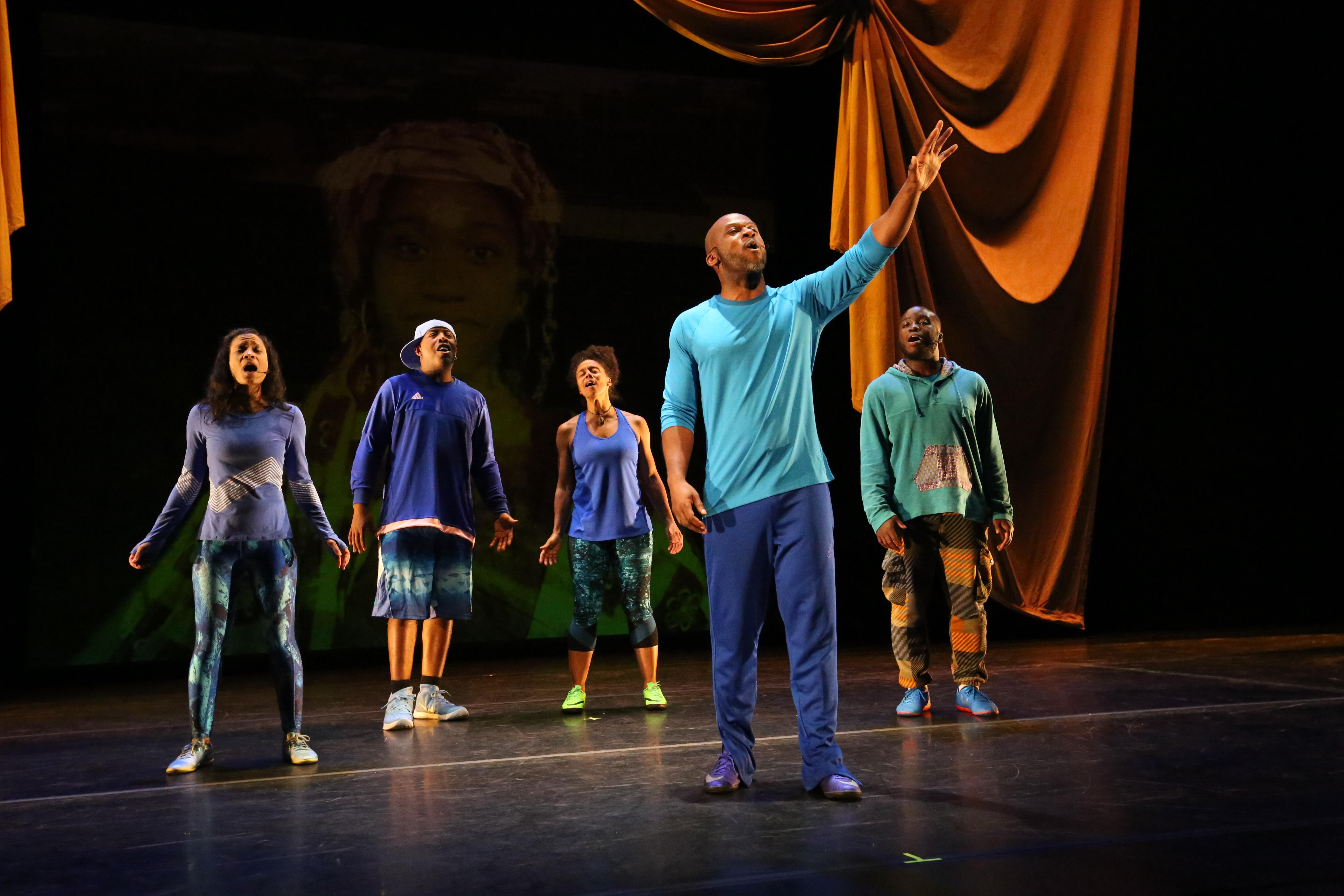 Five performers stand on a stage heads upraised and mouths open. They are dressed in athletic shoes and clothes in shades of blue. In the background, an elaborate umber drapery frames a faintly projected image of a young girl.