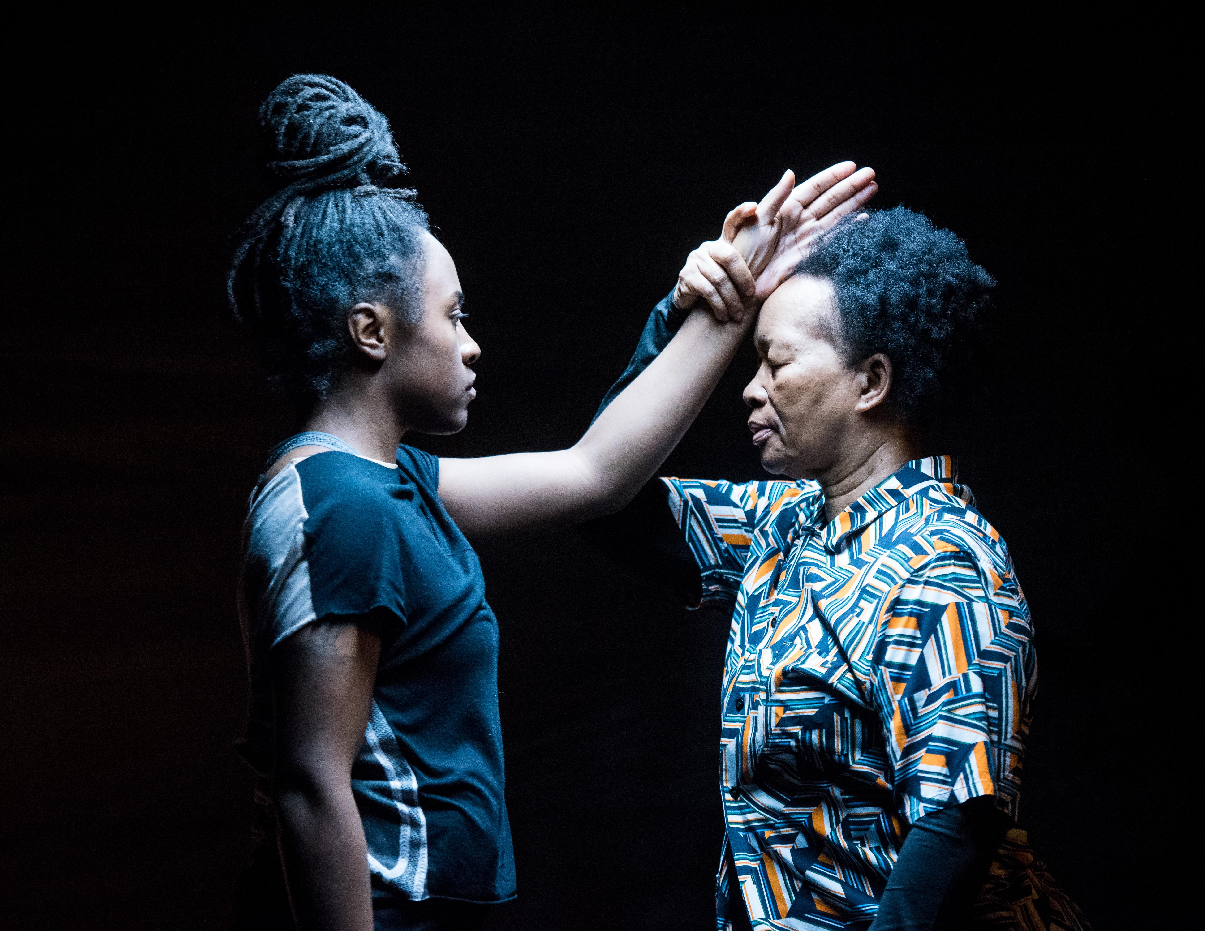Two black women face one another eyes closed under a harsh fluorescent light. The older woman on the right holds the younger woman's outstretched arm by the wrist at her temple.