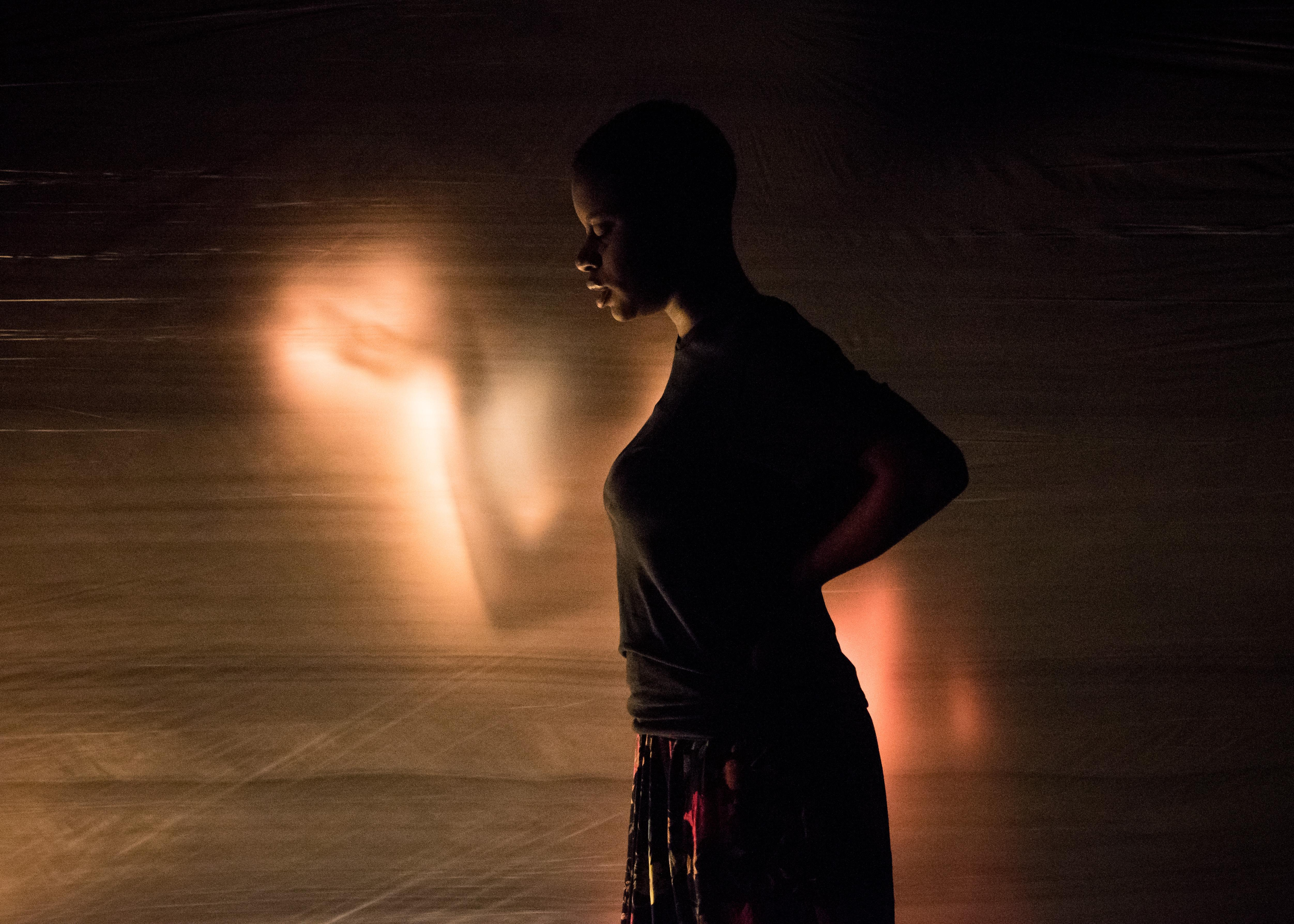 A young black woman in a dark, loose shirt and skirt stands in profile, her hands resting on the small of her back. Behind her we see the hazy glowing figure of upraised arms.