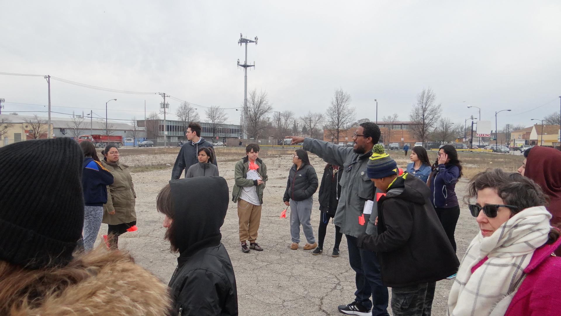 A group of people stand around an empty lot on a cold gray day. A figure in the center points to the left and several people look in that direction.