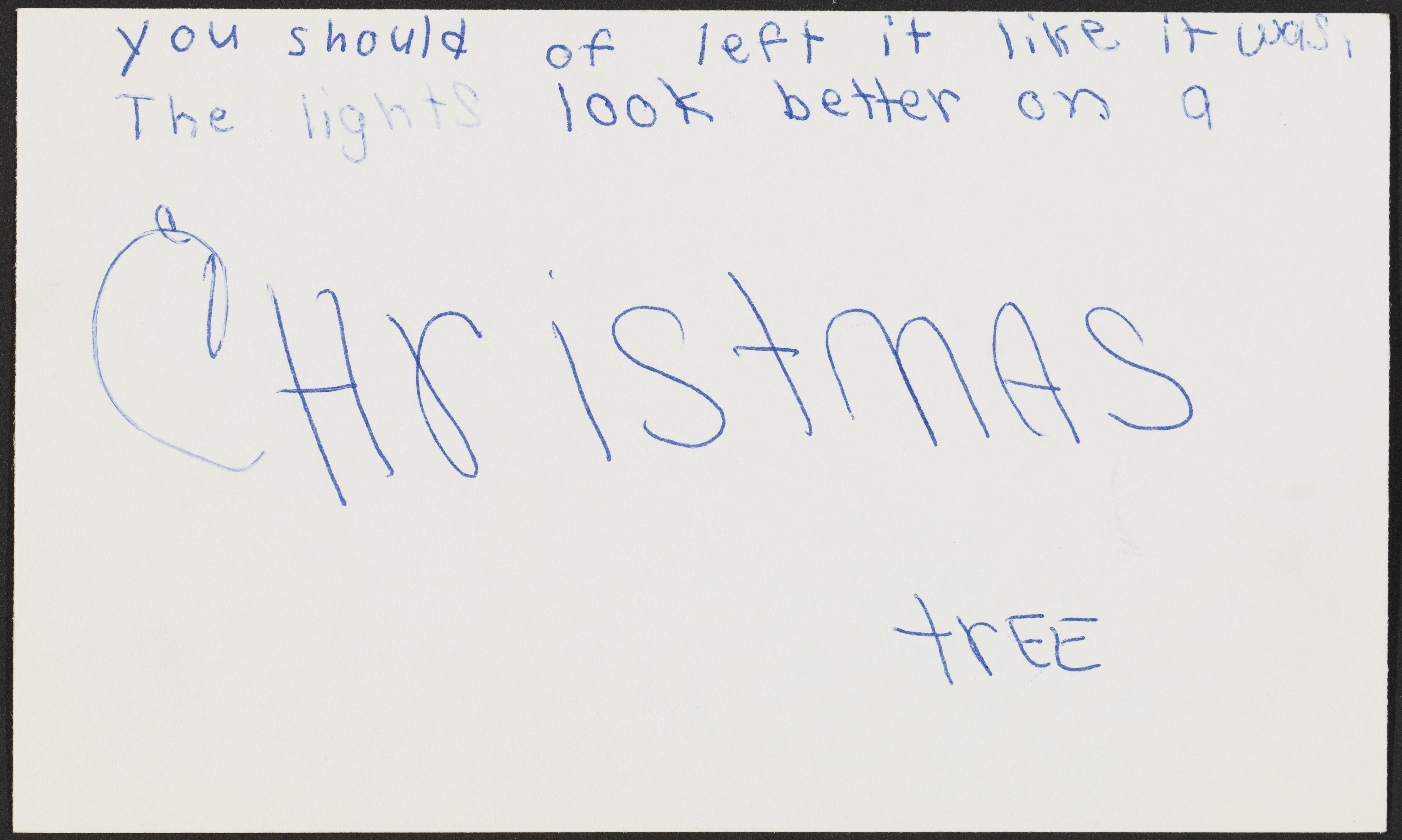 """An index card with handwritten text reads """"you should of left it like it was, the lights look better on a Christmas tree."""" The word """"Christmas"""" takes up most of the index card."""