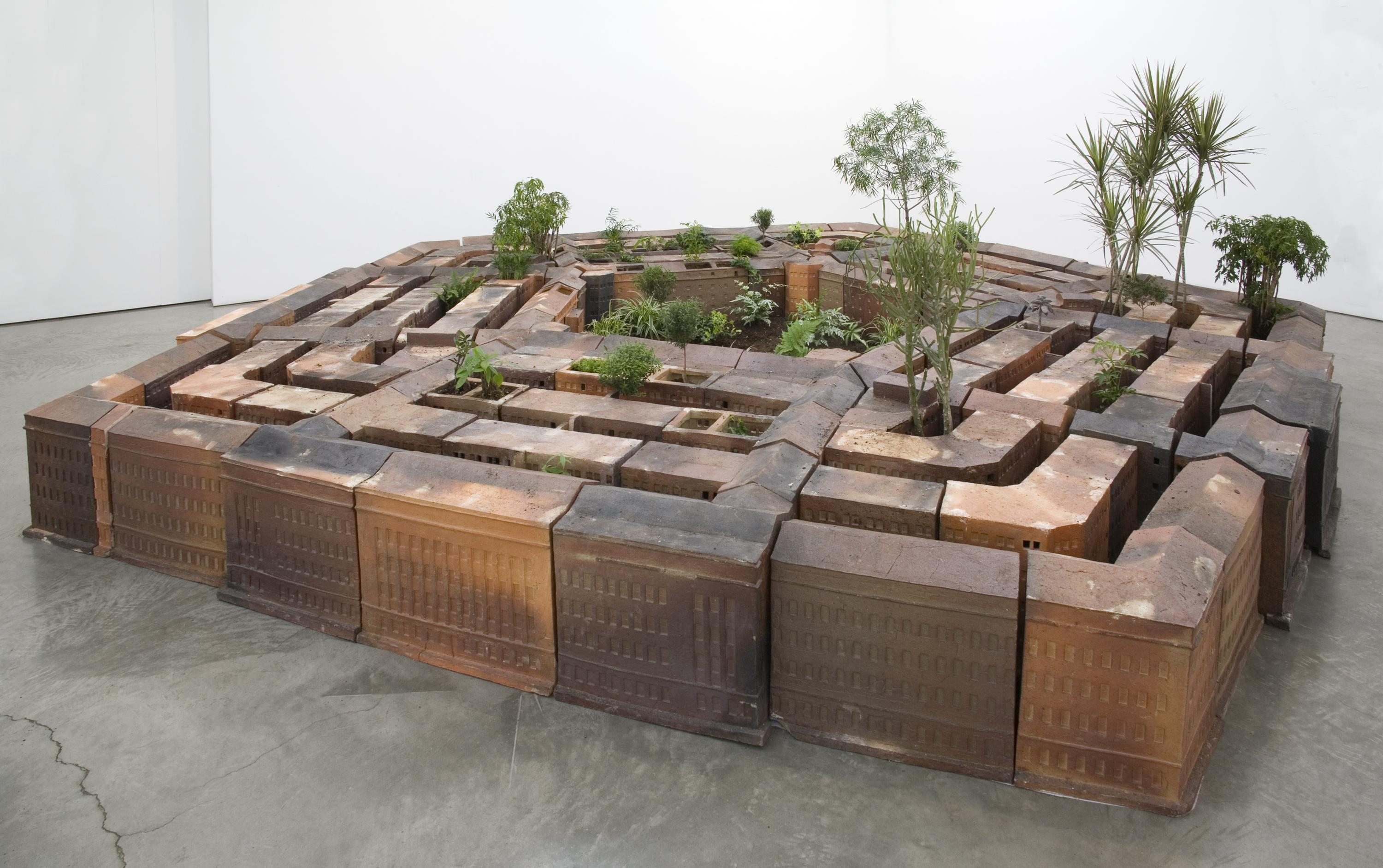 A ceramic model resembles the United States government building the Pentagon, with plants emerging from the alleyways and center open-air space.
