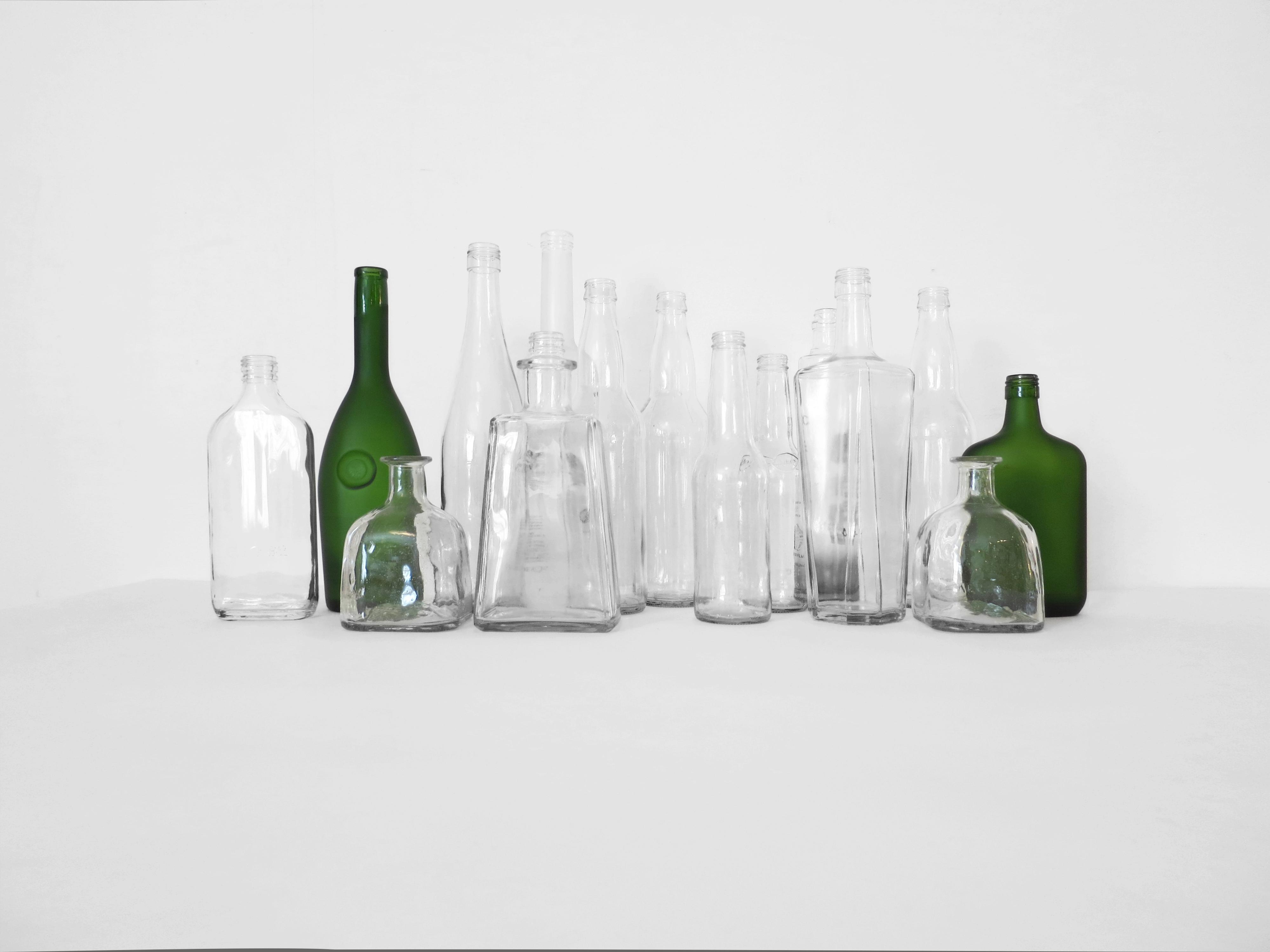 Thirteen colorless glass bottles and two green bottles, each a different shape and size and without a label, stand in a cluster in front of a white wall.