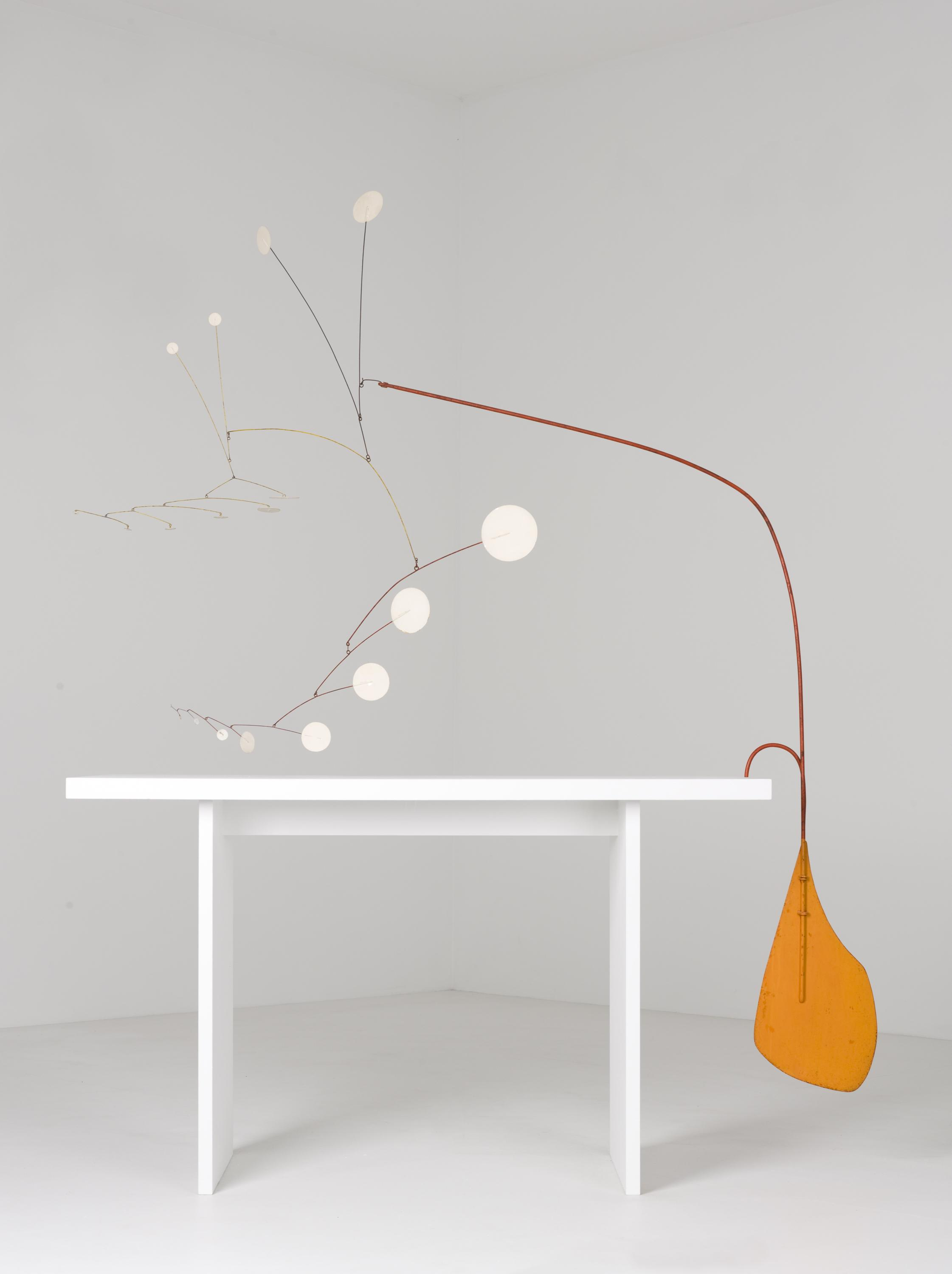 Small white circles connected by thin wire balance opposite a thicker orange wire weighted by an orange rudder-like shape hanging from the edge of a white table.