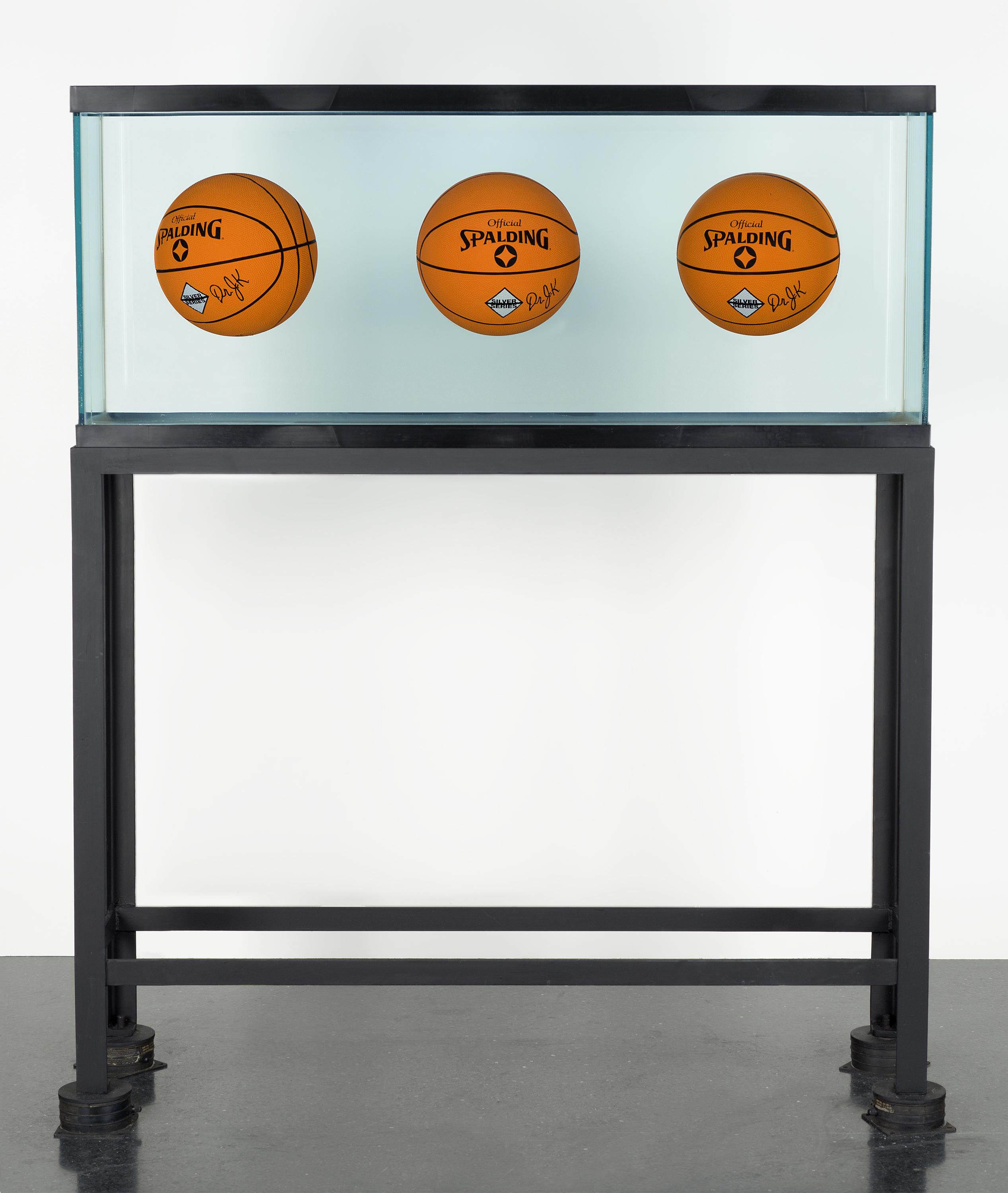 Three orange Spalding basketballs float in the middle of a rectangular fish tank.