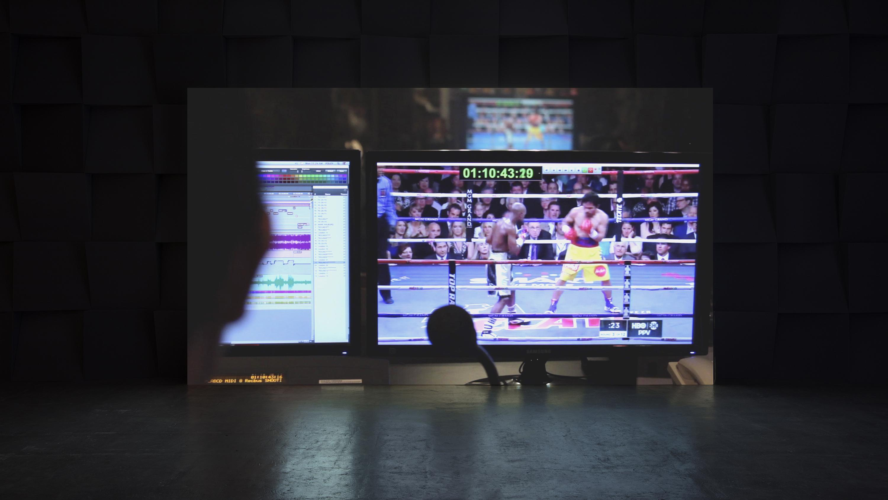 Projected on the wall of a dark room is the image of two monitors, one playing a boxing match, the other showing multiple bars of sound waves.