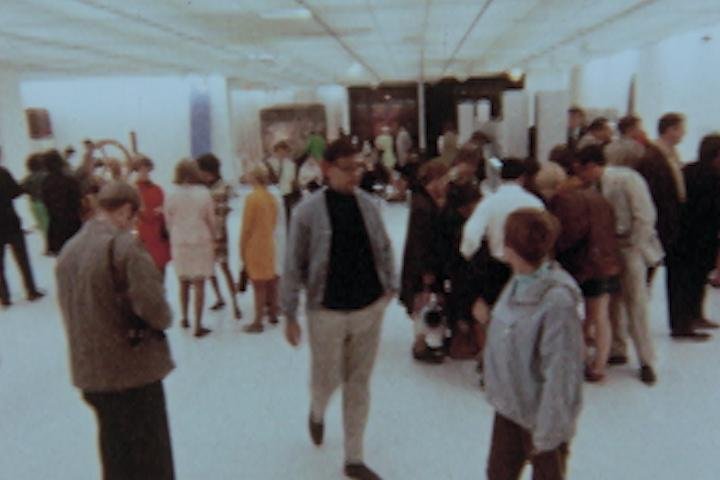 A vintage video still shows a busy art gallery filled with people looking at artworks and talking with one another.