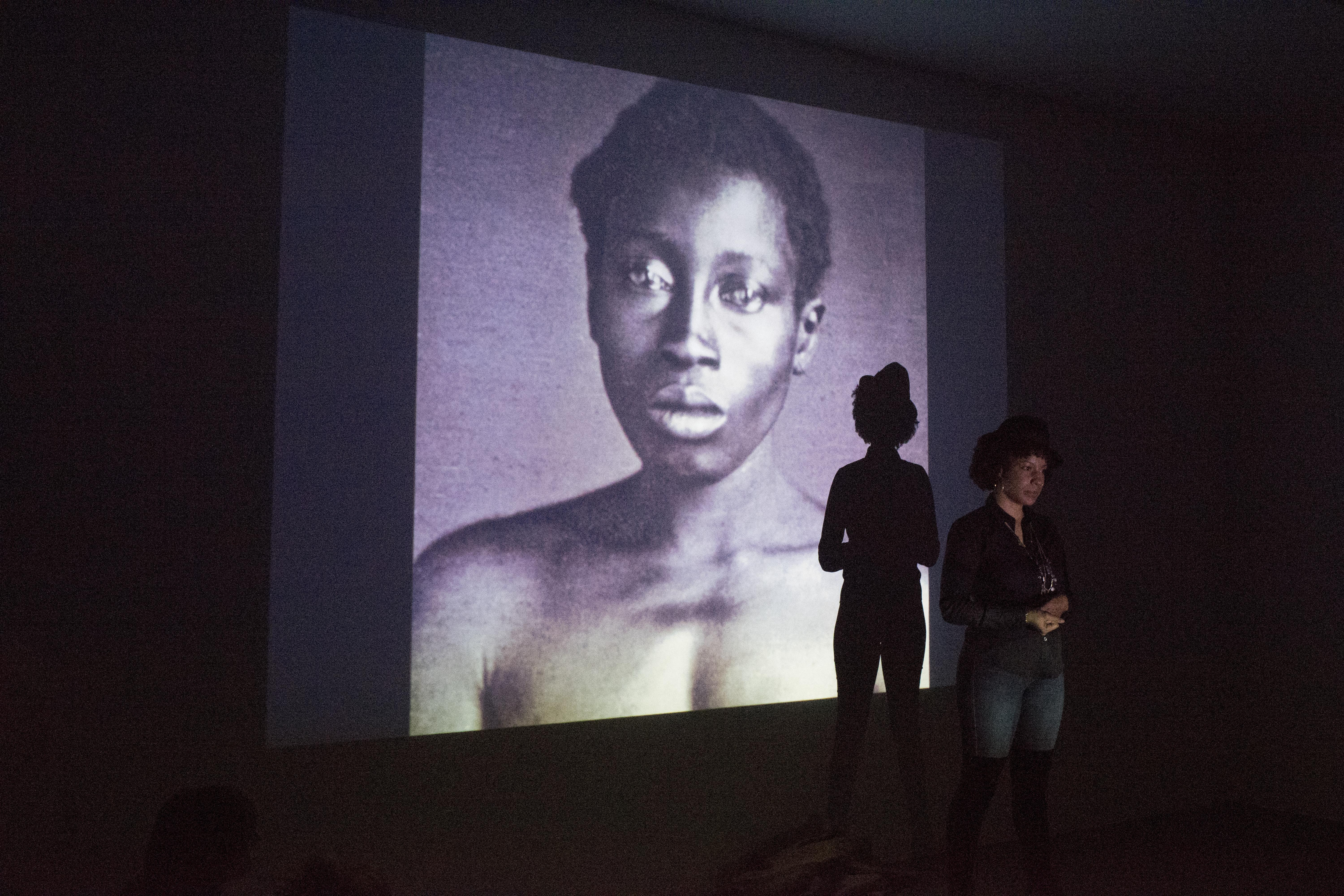 A black woman stands in front of a large projection of a topless, black woman.