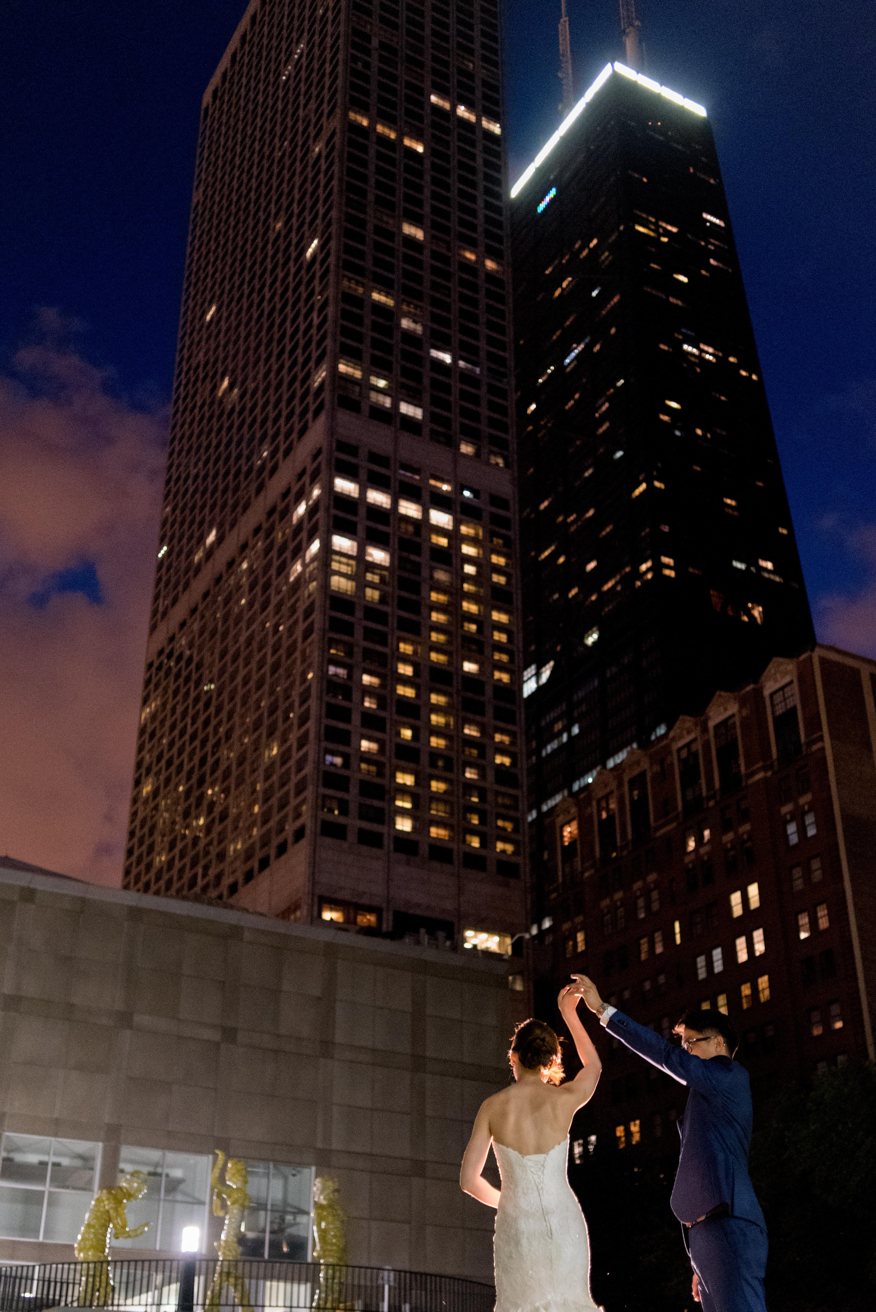 A woman in a white wedding dress and a man in a navy suit dance in the MCA's backyard with tall skyscrapers, including the John Hancock building, as the backdrop.