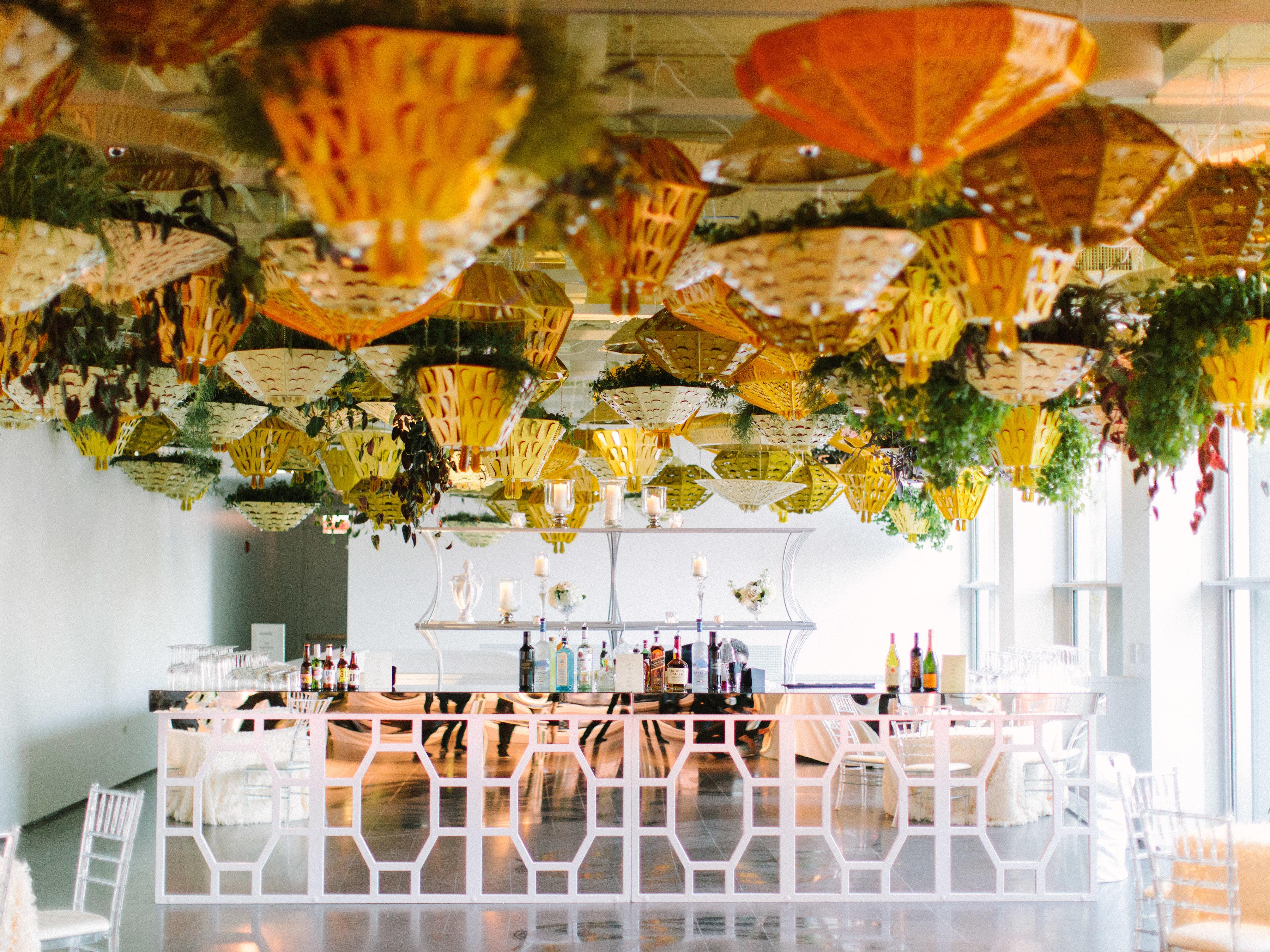 Bright light floods a room from a wall of windows. Vibrant, warm-colored planters hang above a well-stocked bar.