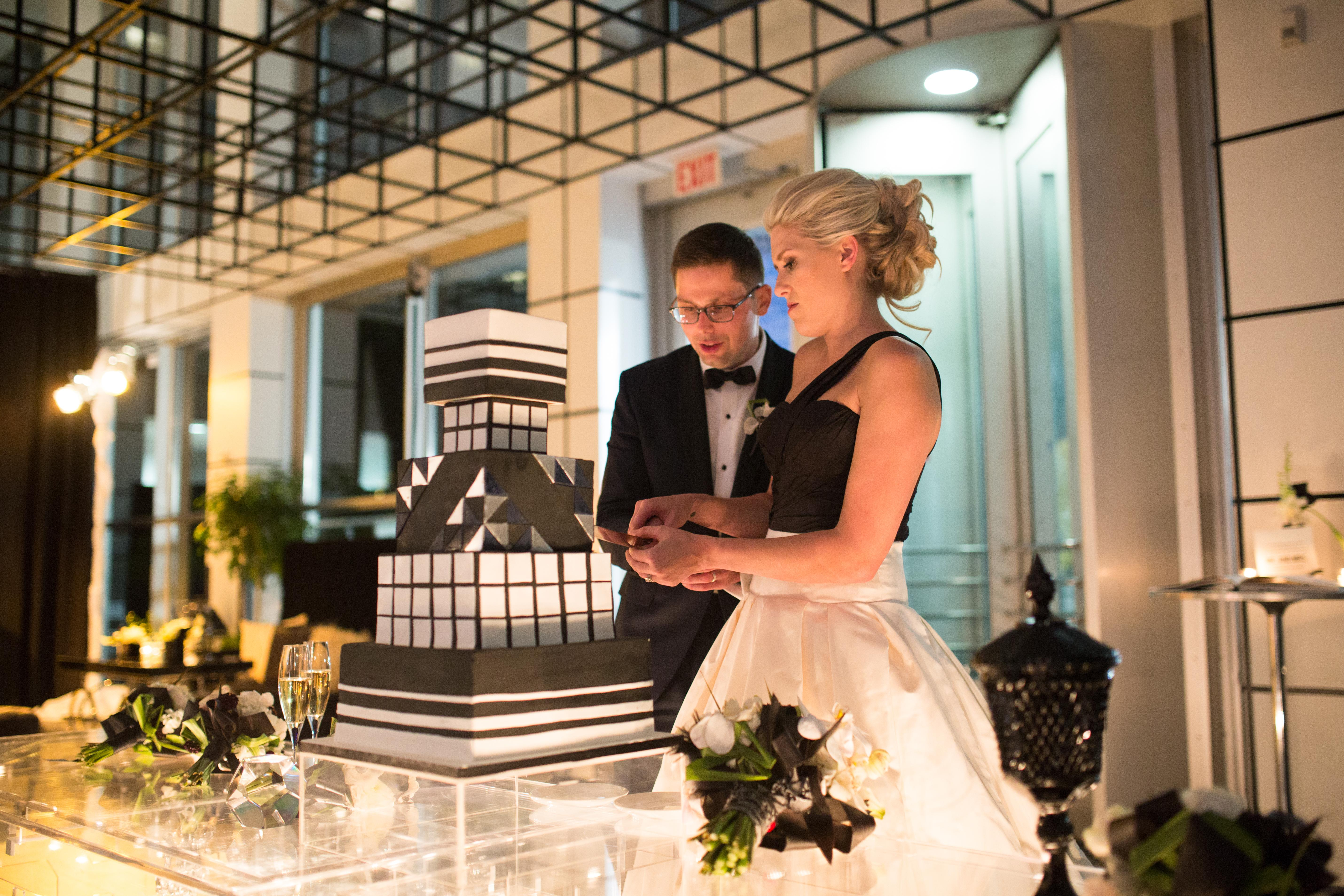 A light-skinned bride in a black-and-white gown stands next to a groom in a black tuxedo. they cut into a black-and-white, many-layered geometric cake that is similar to a black cube-like structure above them.