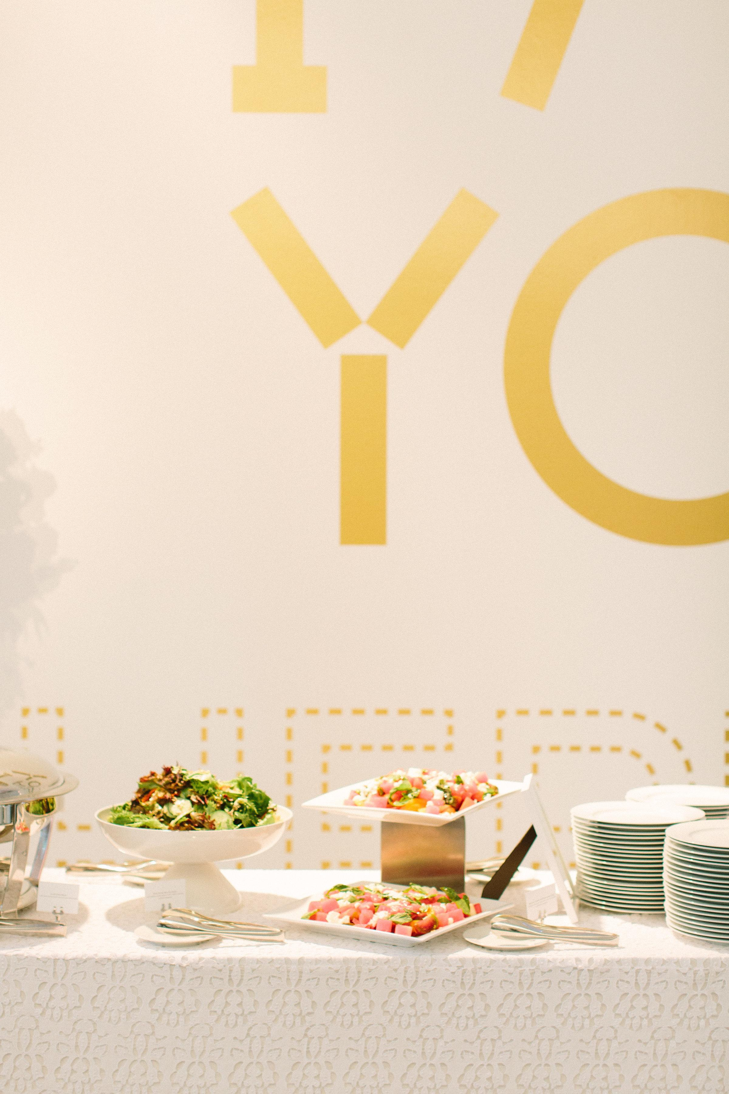 An elegant display of green and watermelon salads are displayed on white tableware besides stacked white plates on a contemporary-patterned white tablecloth.