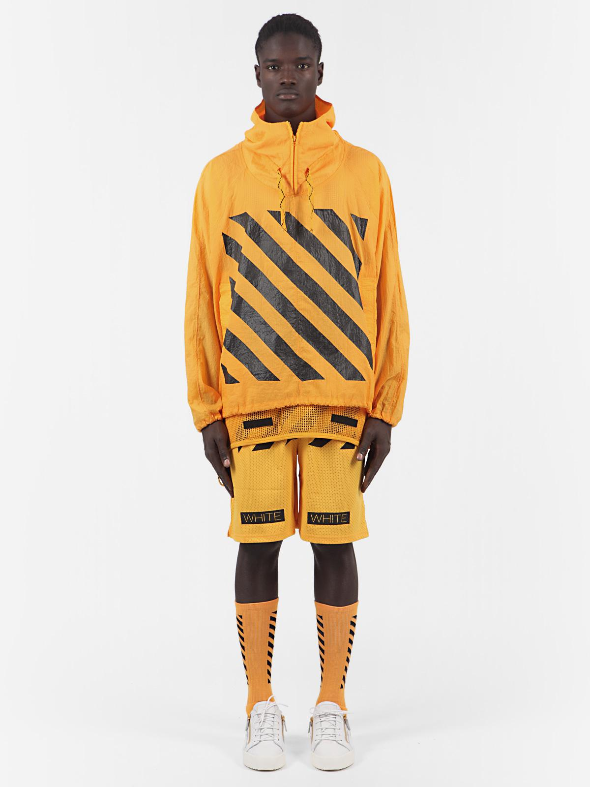 A dark-skinned model stands rigidly while wearing a rich yellow outfit of a striped hoodie, long shorts, and high striped socks with white sneakers.