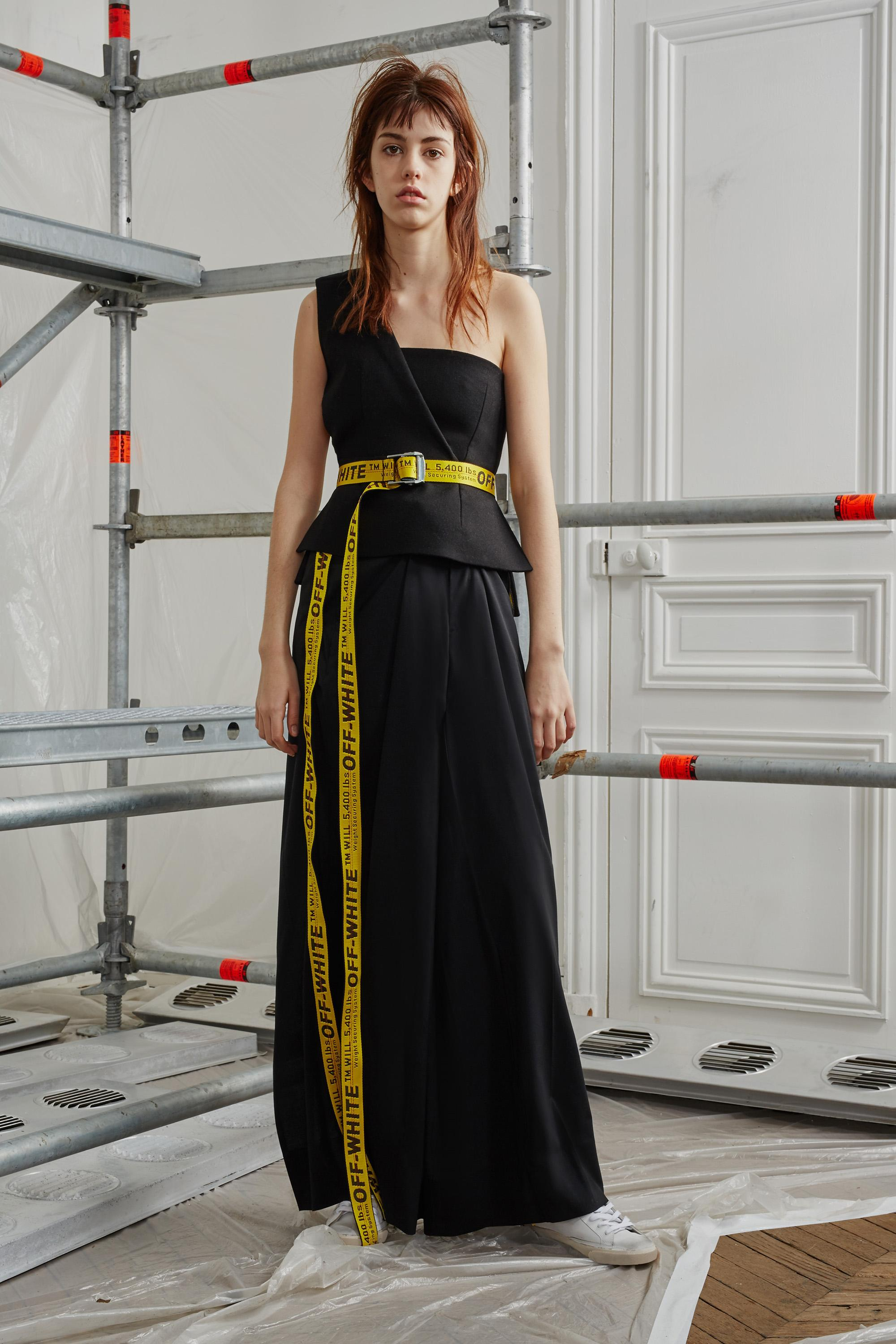 """A pale young woman wears a single-shoulder, floor-length black dress cinched with an industrial-yellow belt with black lettering that reads """"OFF-WHITE"""" and that drapes down to her white sneakers."""