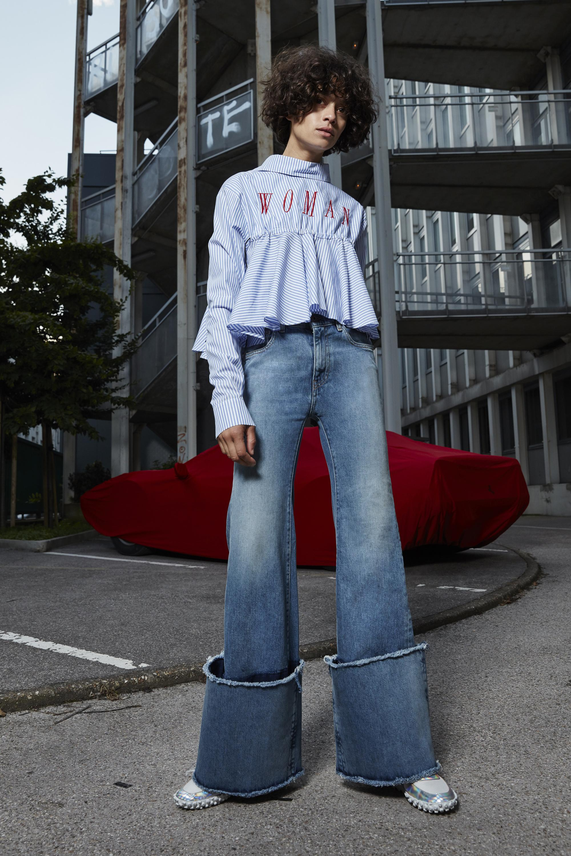 """A model poses in an urban landscape while wearing a frilly shirt with the word """"WOMAN"""" on the breast and wide-flared denim jeans."""