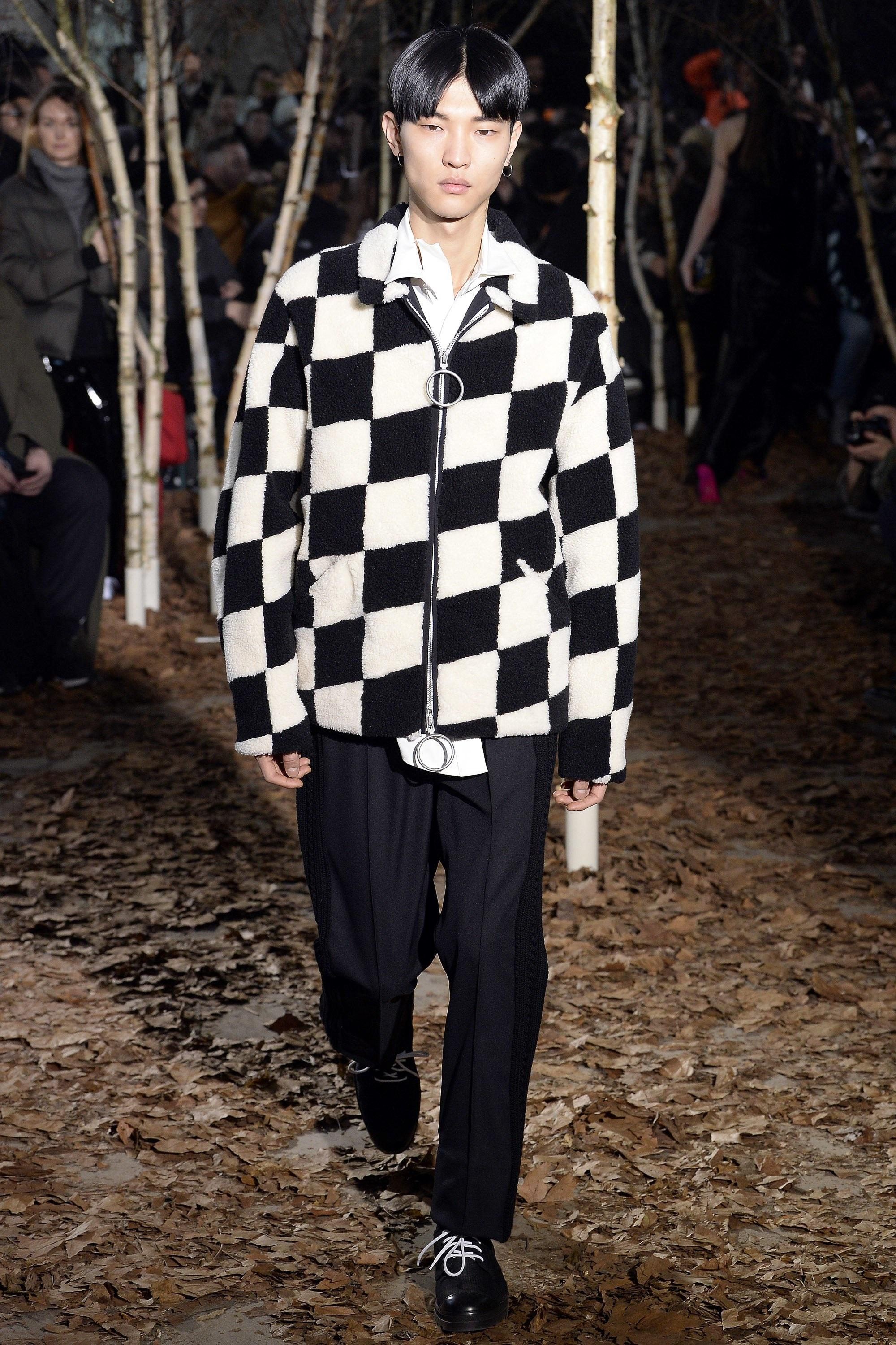 A model walks down a forest-like runway while wearing a boldly checkered black-and-white sherpa fleece jacket and black trousers.
