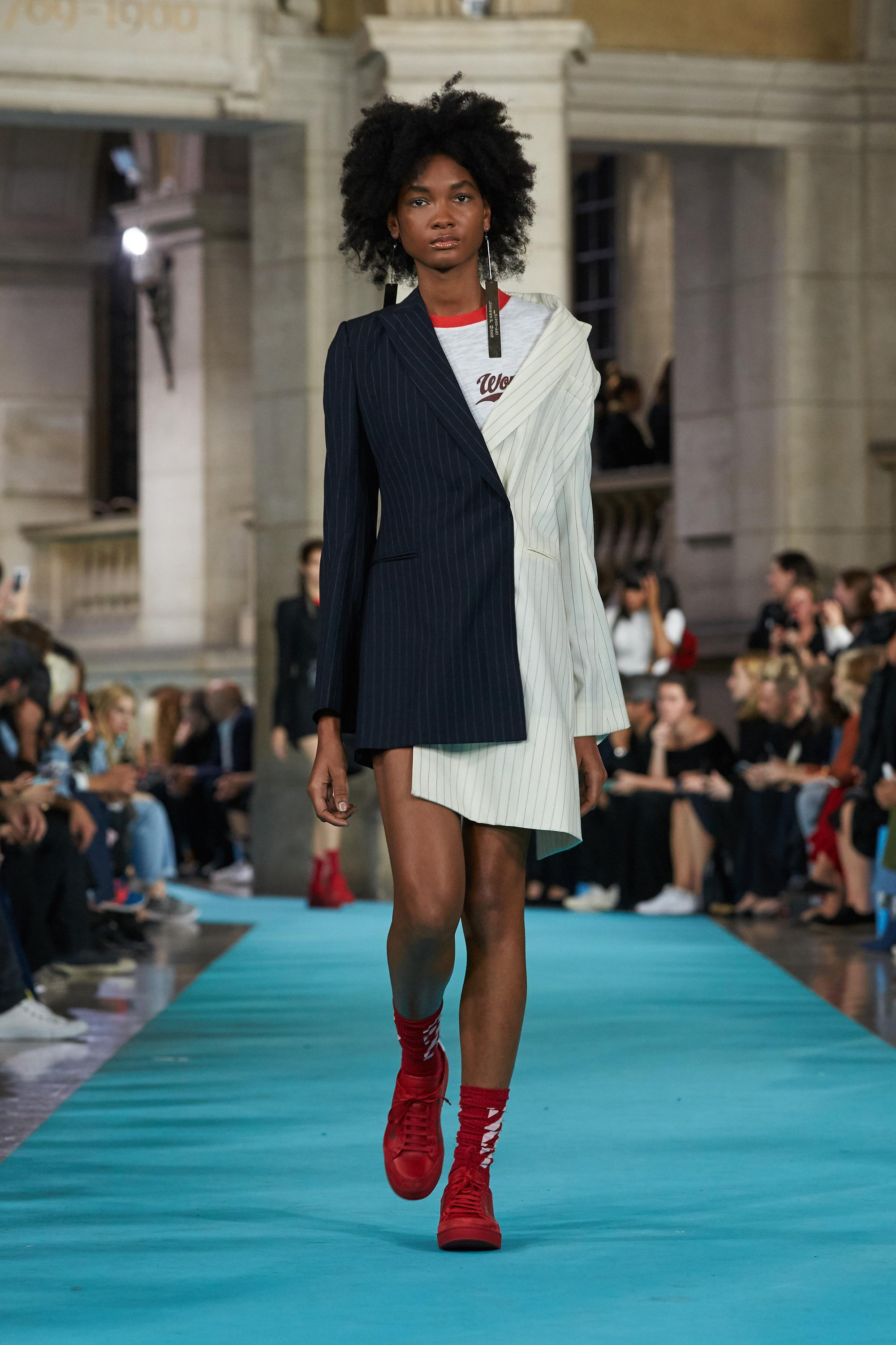 A model walks down a runway while wearing long earrings, an asymmetrical pinstriped suit dress, and red sneakers.