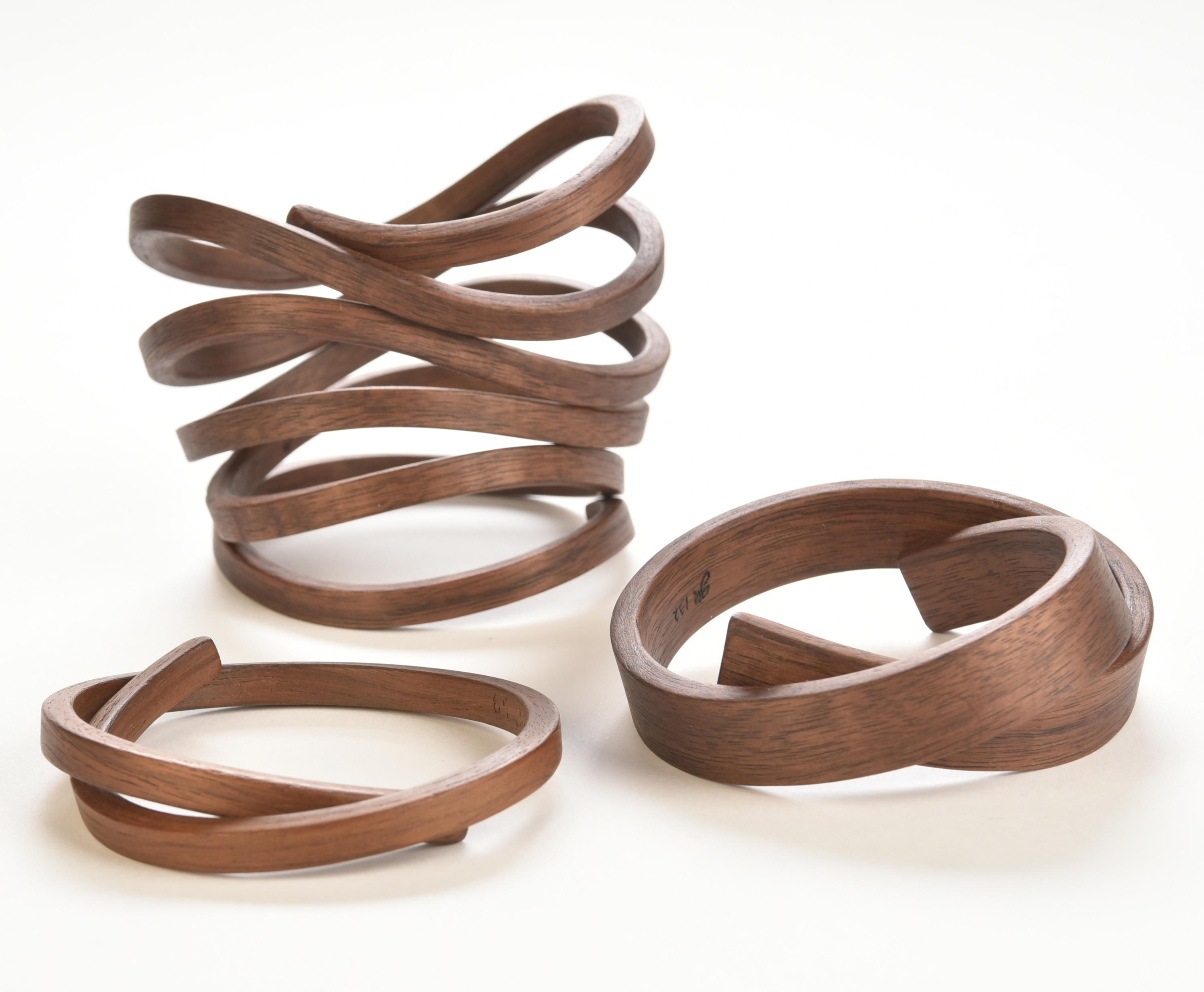 Three wooden bracelets of varying thicknesses are each shaped into distinct spirals.