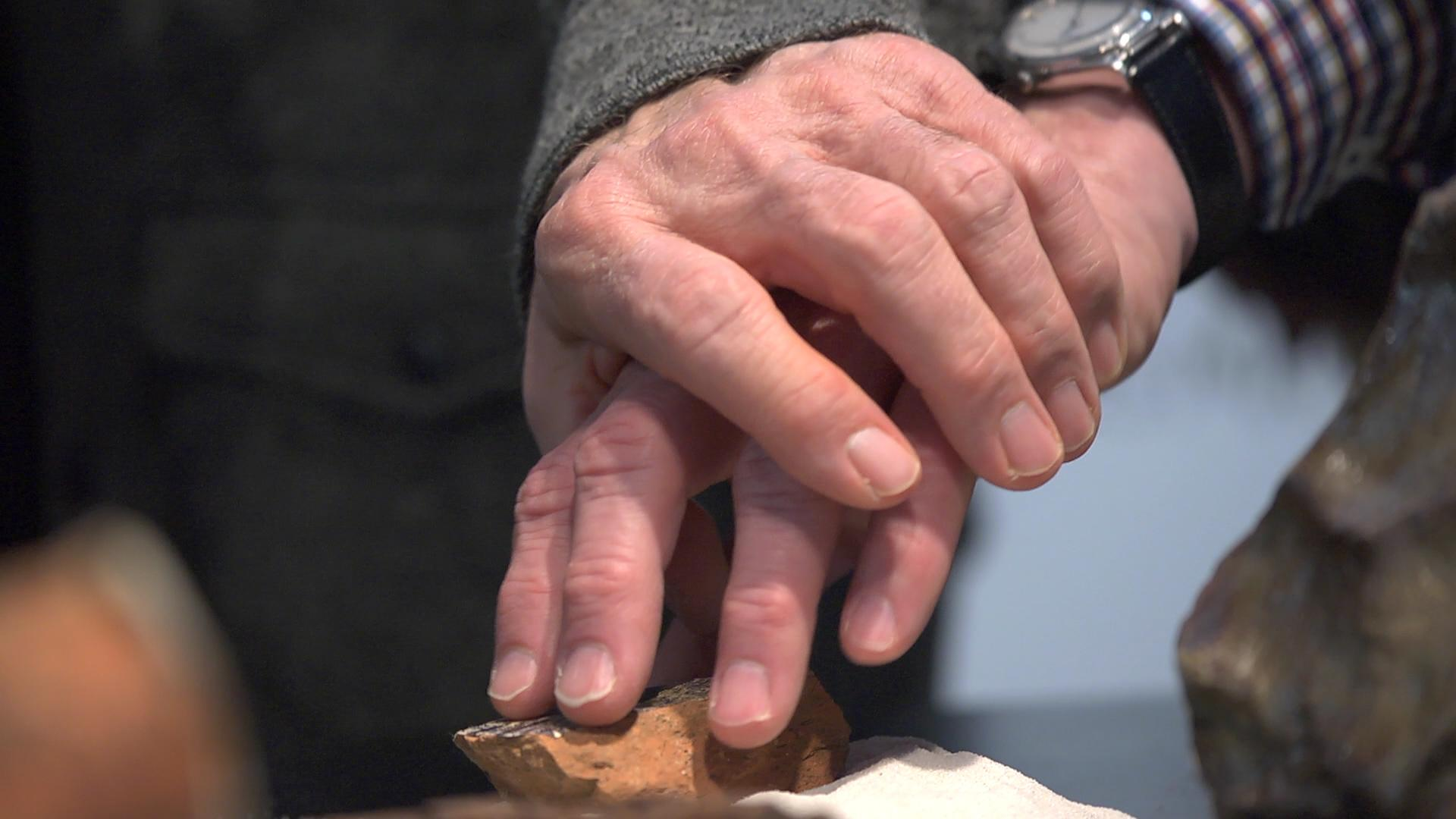 A person holds another person's hand, guiding them to touch the surface of a rock.