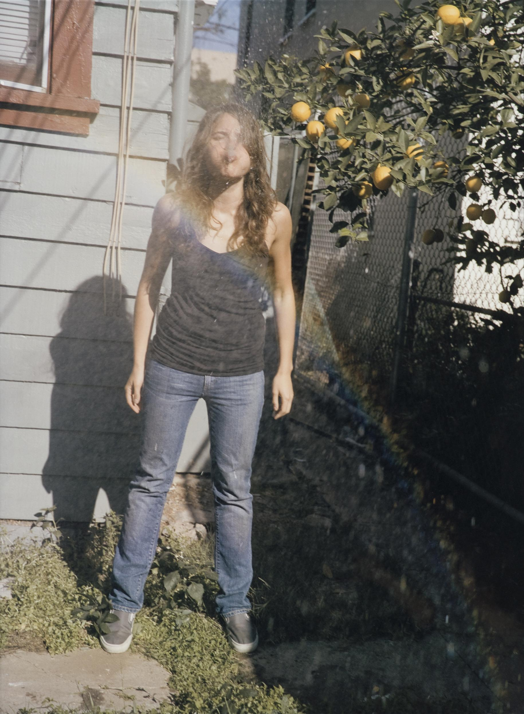 A young woman spits water at you, creating a rainbow through the spray. She stands in a backyard next to a lemon tree.