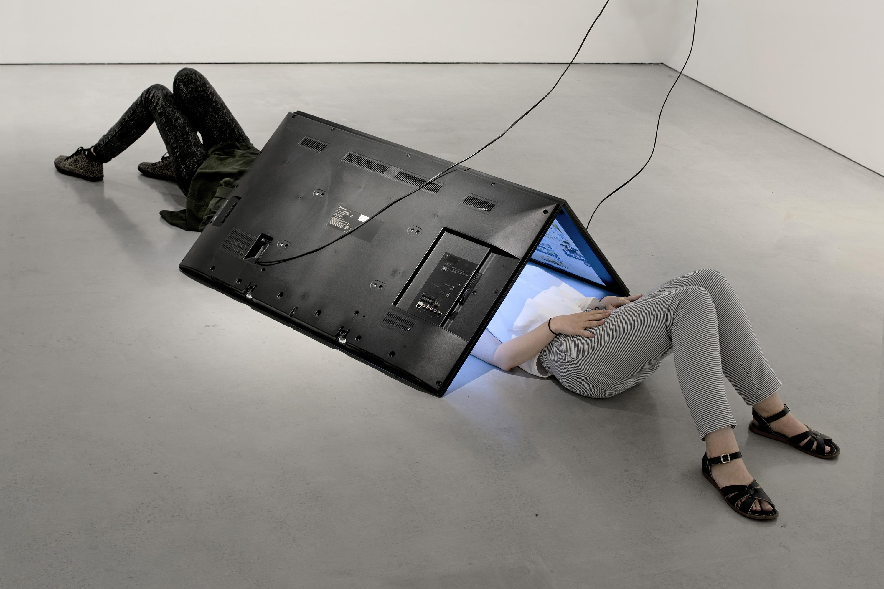 Two people lay on the floor beneath a tent-like structure made from two large digital screens. Their heads are hidden beneath the screens.