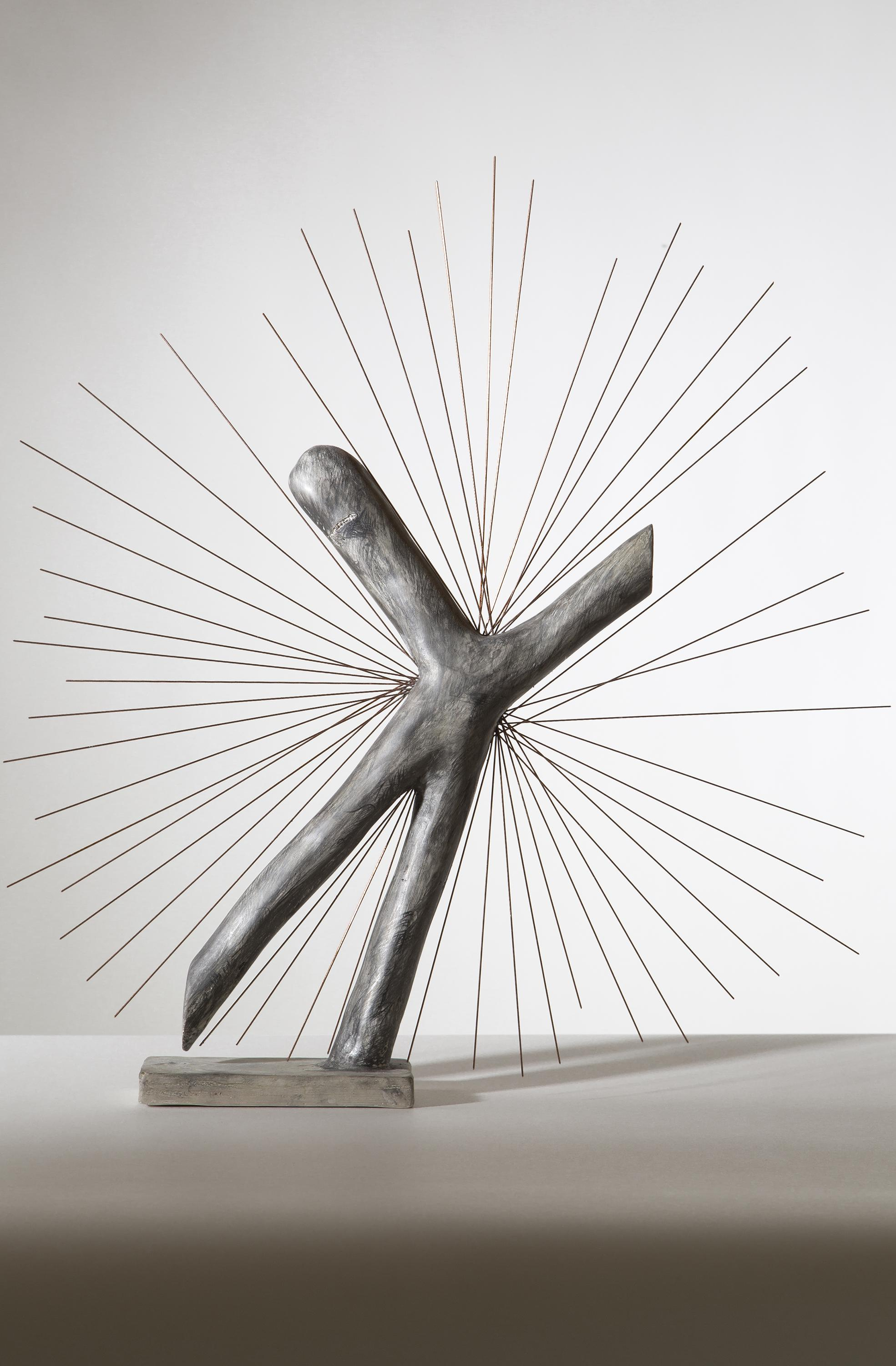 A sculpture shaped like a crooked letter X stands on a short rectangular base. From the center many spokes jut out creating a starburst effect.