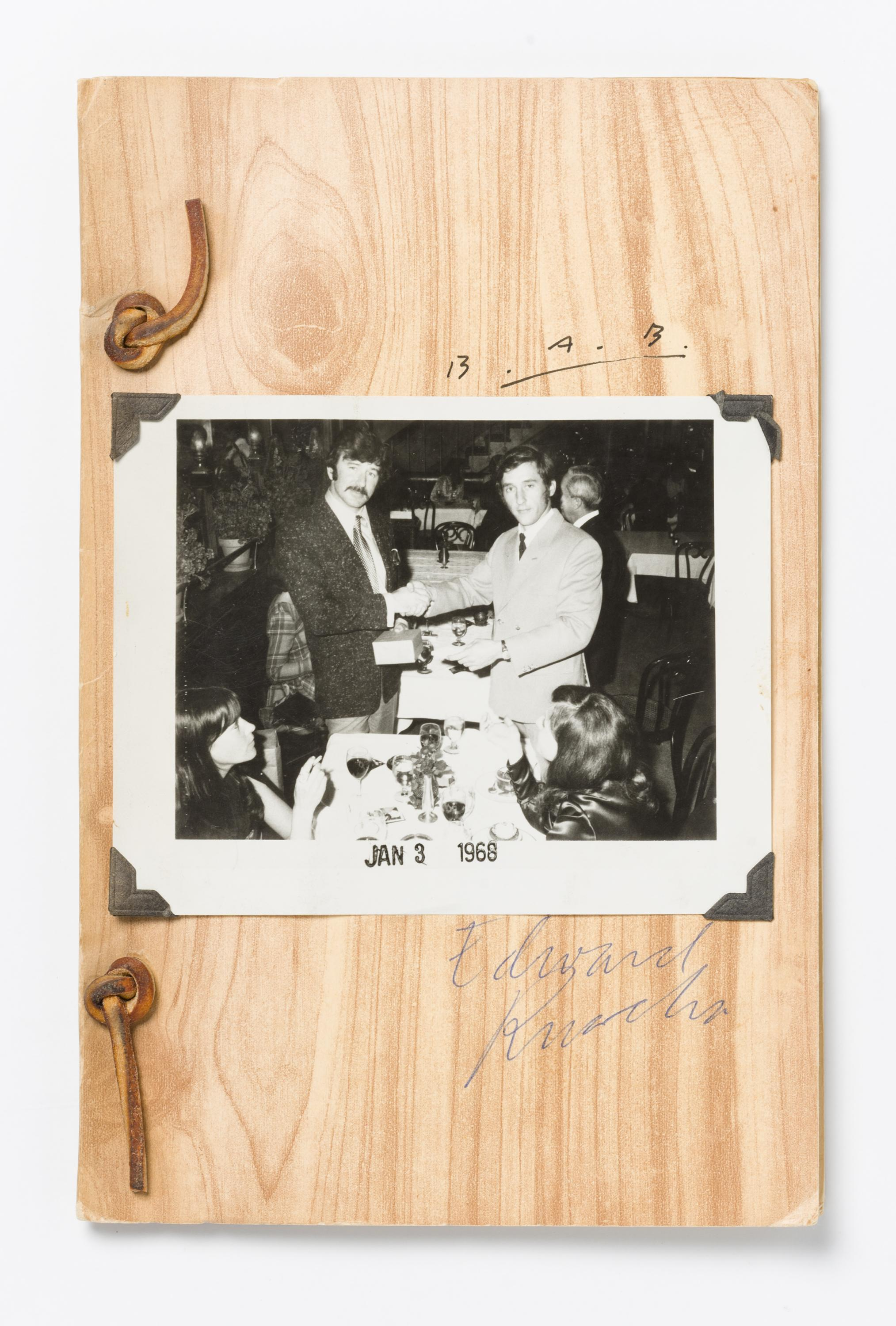 A black-and-white photograph of two men shaking hands is mounted to a light-colored piece of wood.