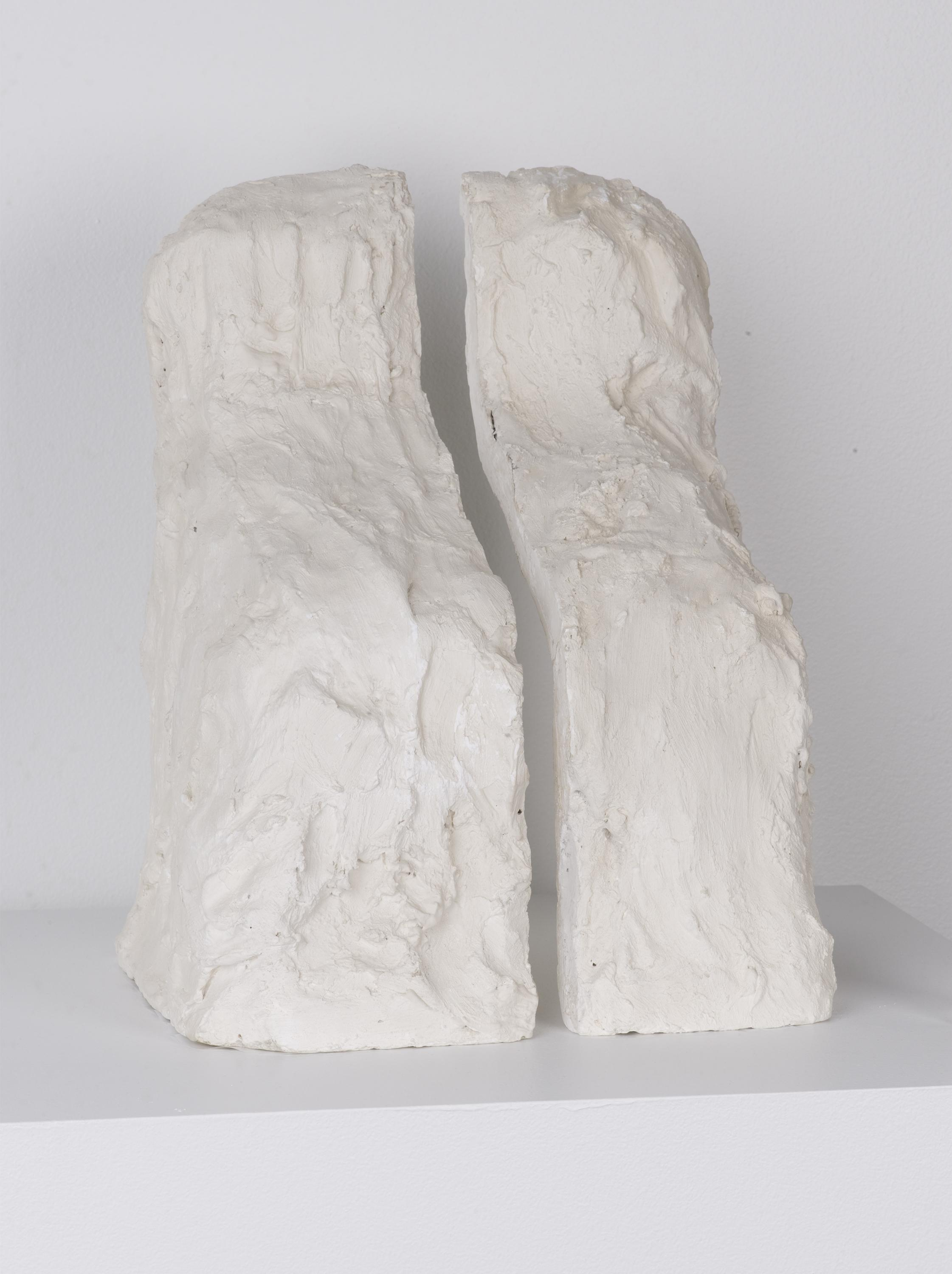 A messy white plaster form has been cleaved into two halves, like bookends.