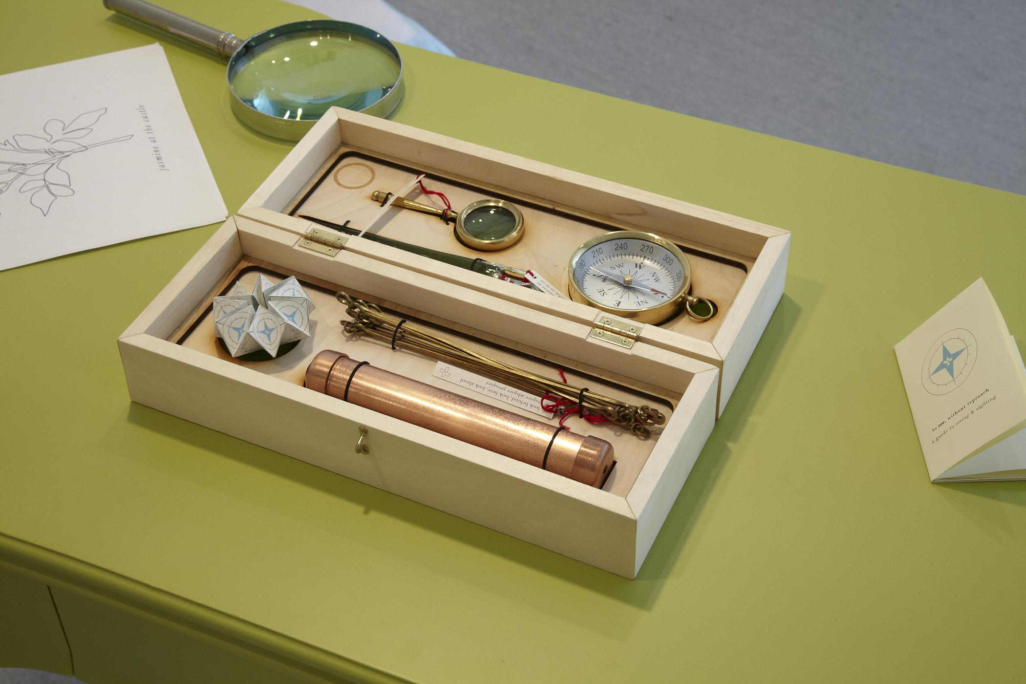 A box made of light wood holds small tools like a magnifying glass, compass, and telescope. It rests on a table alongside a larger magnifying glass and two written materials.