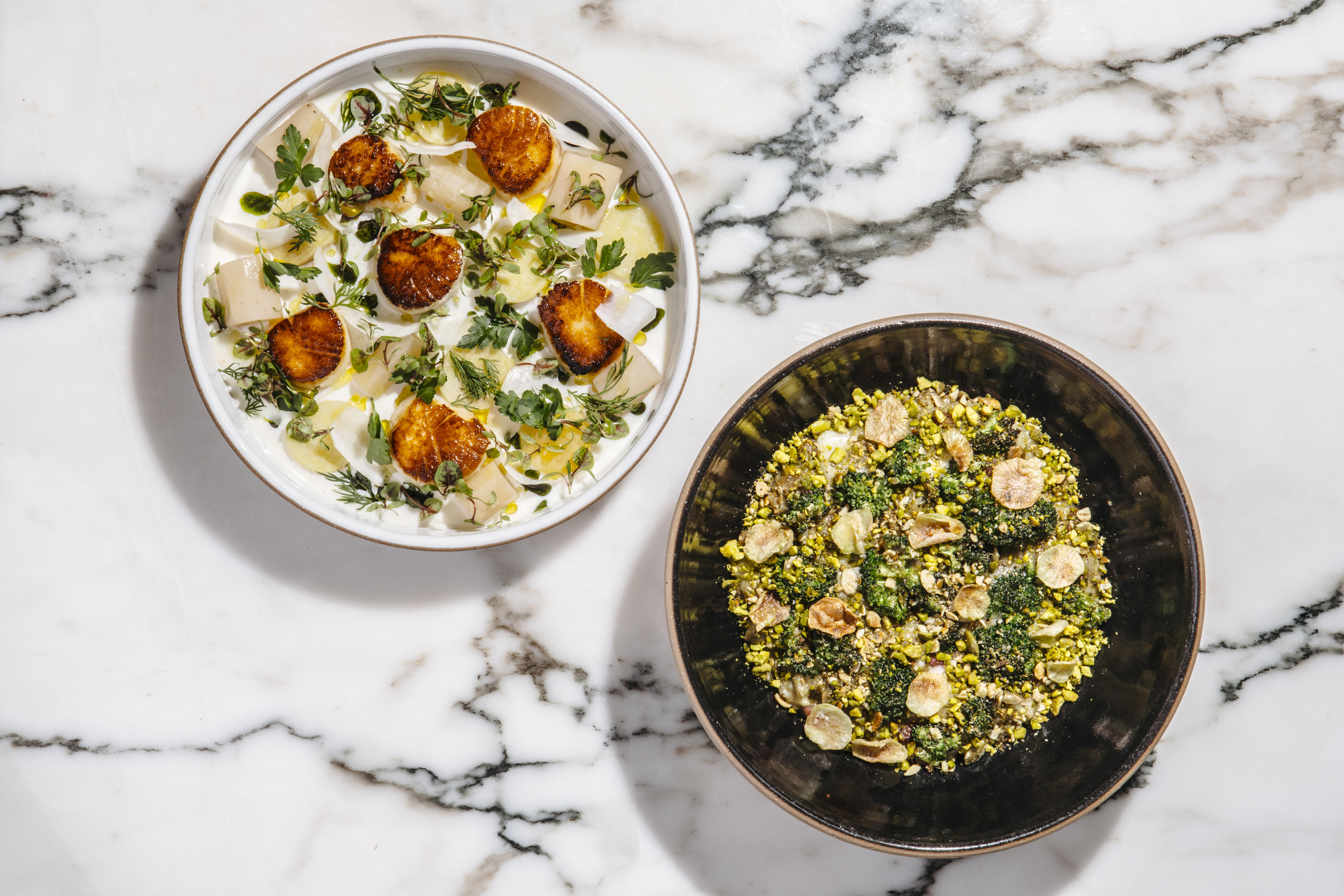 Two dishes are plated and served atop a white marble surface. The dish on the left is light, with greens and six scallops. The dish on the right appears more dense.
