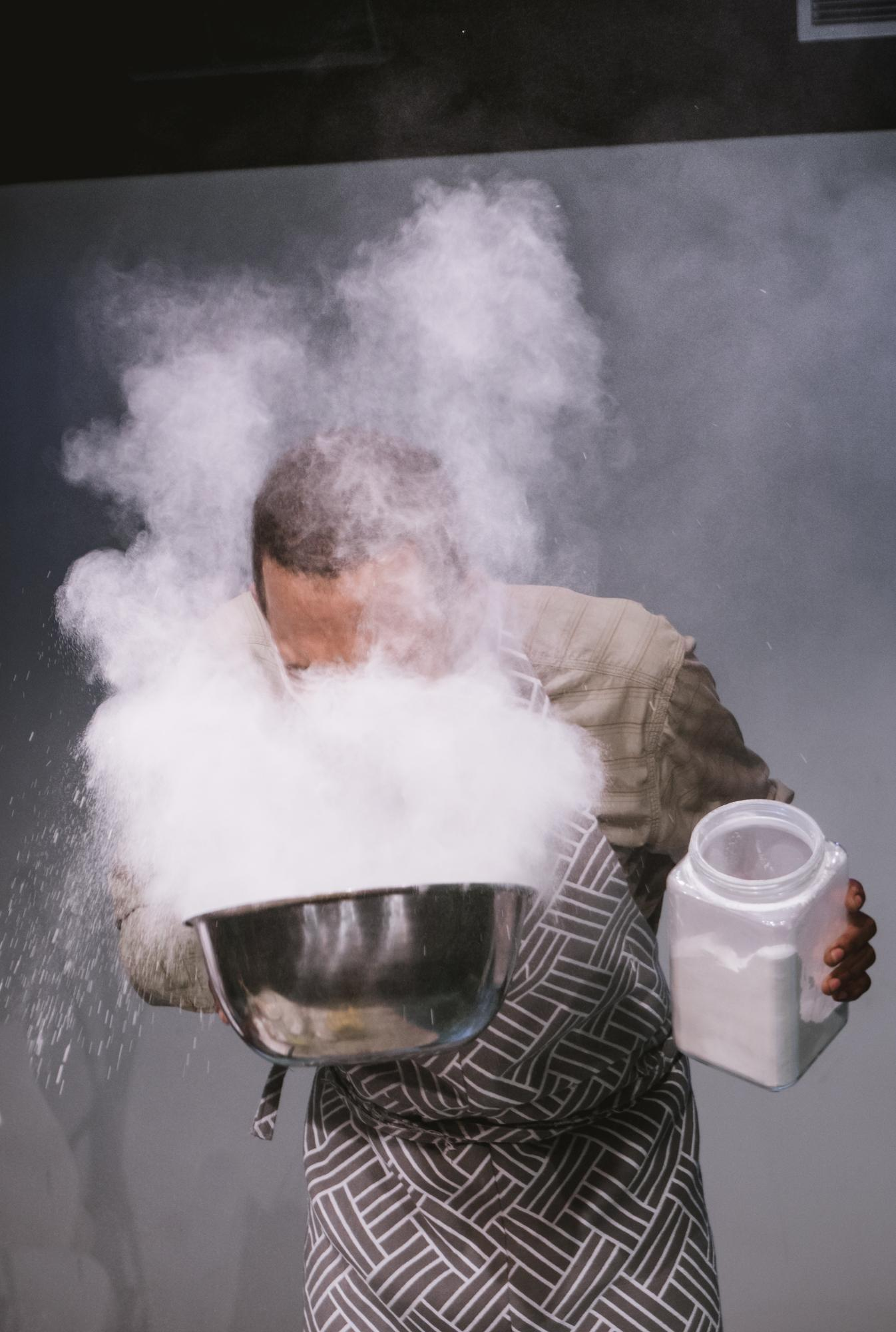 A man bends at the waist to blow into a large metallic bowl full of a white powder. The powder plumes into his face and around his head, obscuring his facial features.