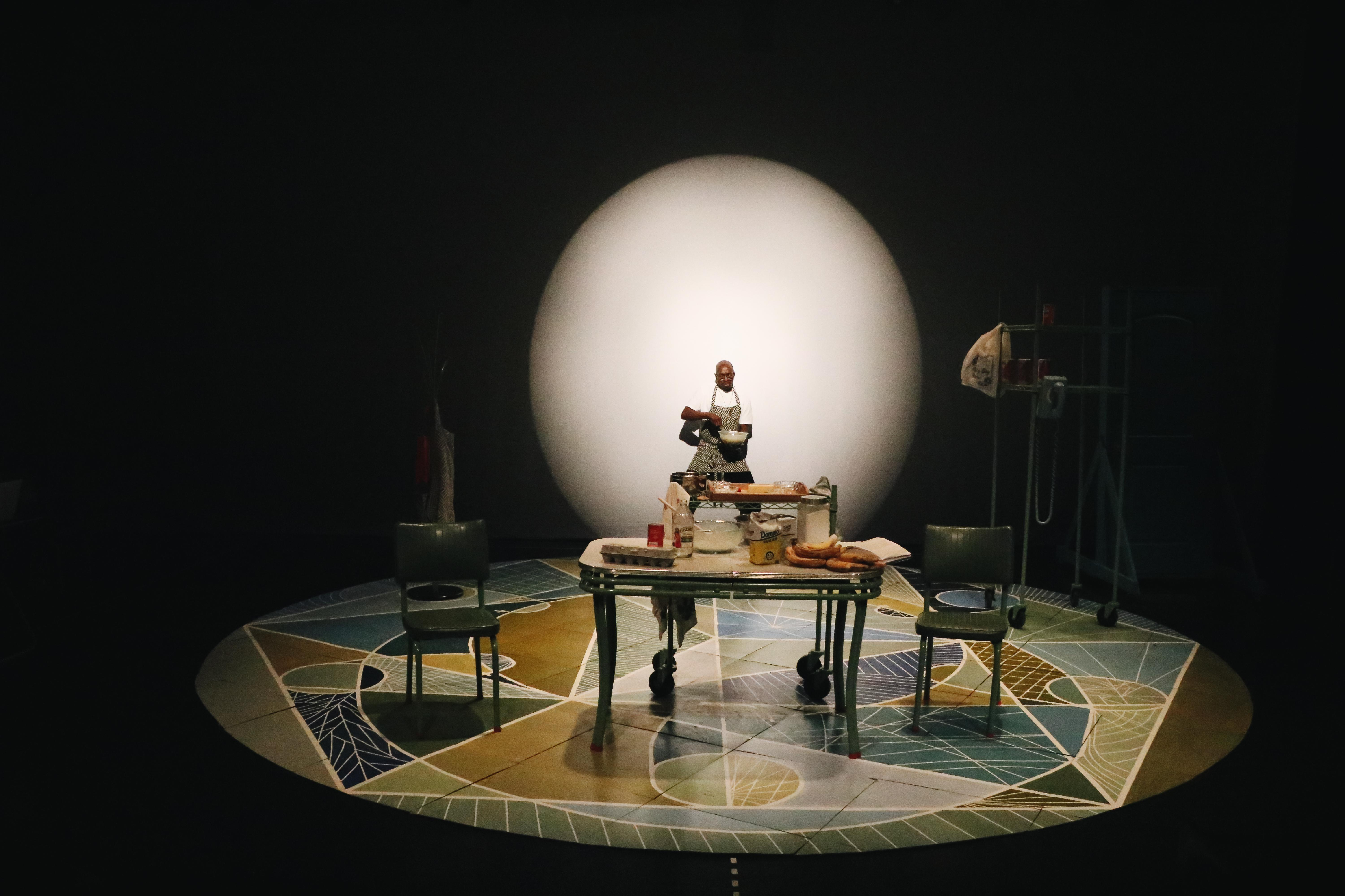 A dark-skinned man stands on a stage set like a kitchen with a mosaic circular floor and a large white sphere looming behind him.