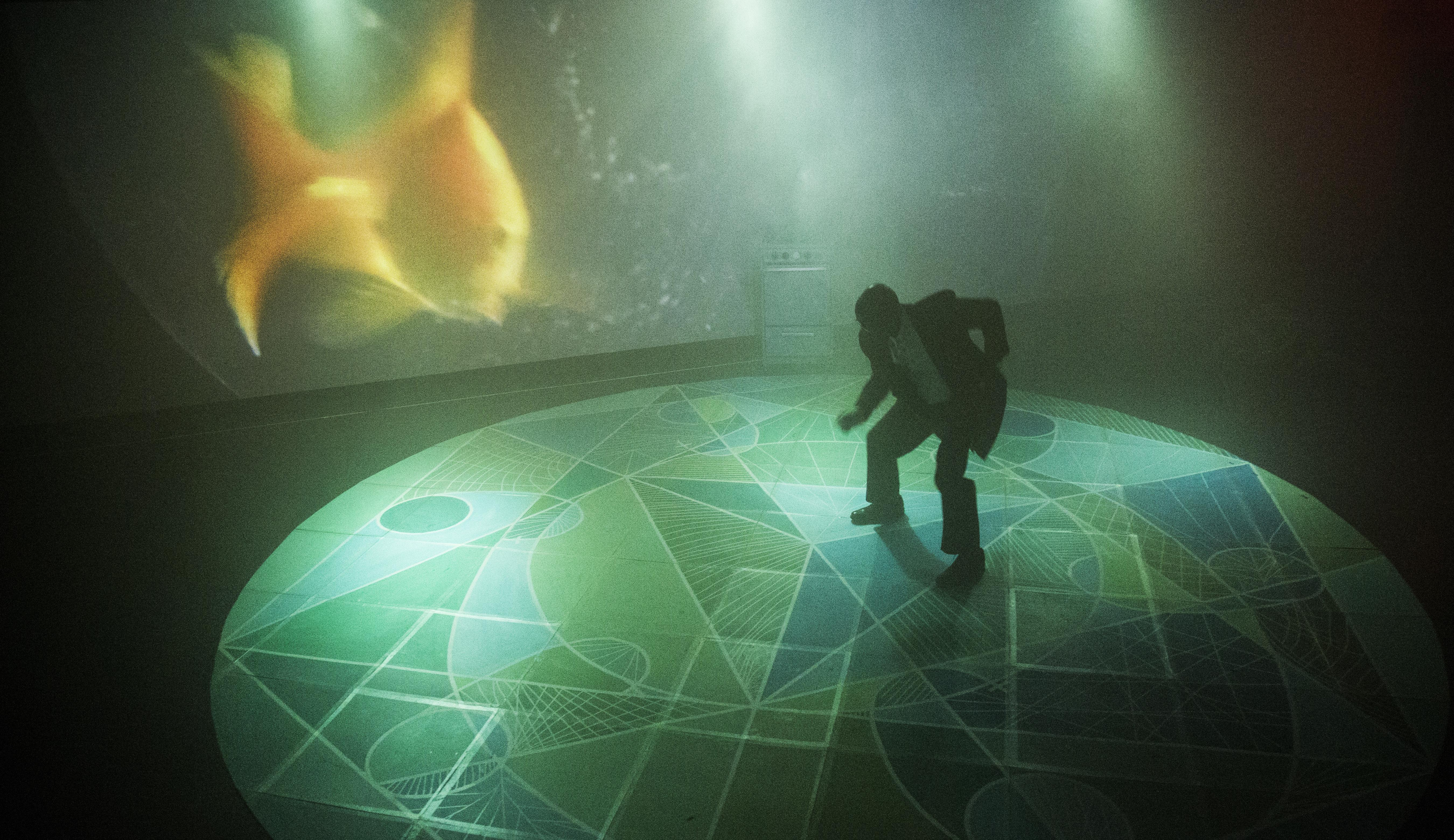 A man in a businesslike suit crouches as if dancing on an illuminated stage. The floor beneath him features an intricate pattern of various greens, while the screen behind him shows a blurry projection of a goldfish.