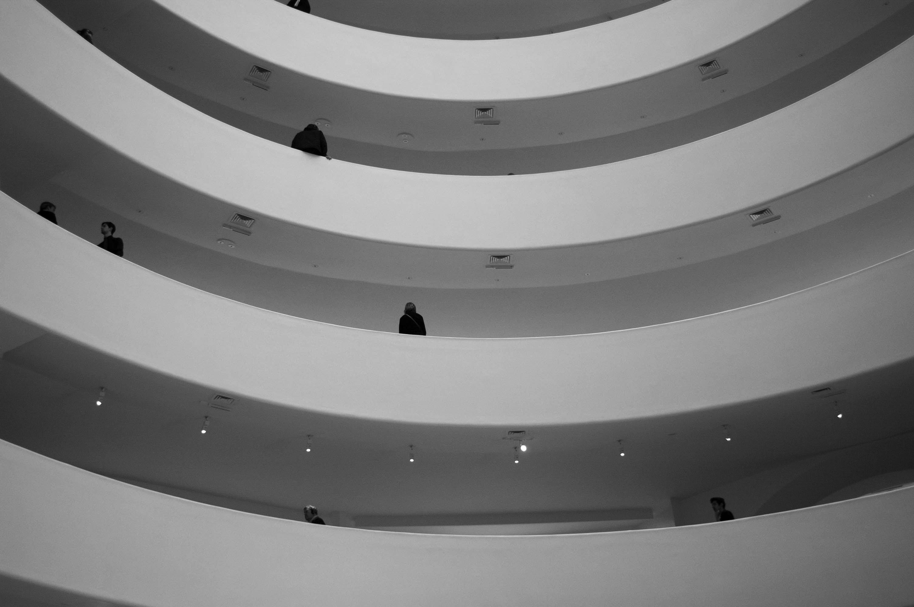 Taken from a lower level looking up, a black-and-white photo shows four levels of a building that curve inwards.