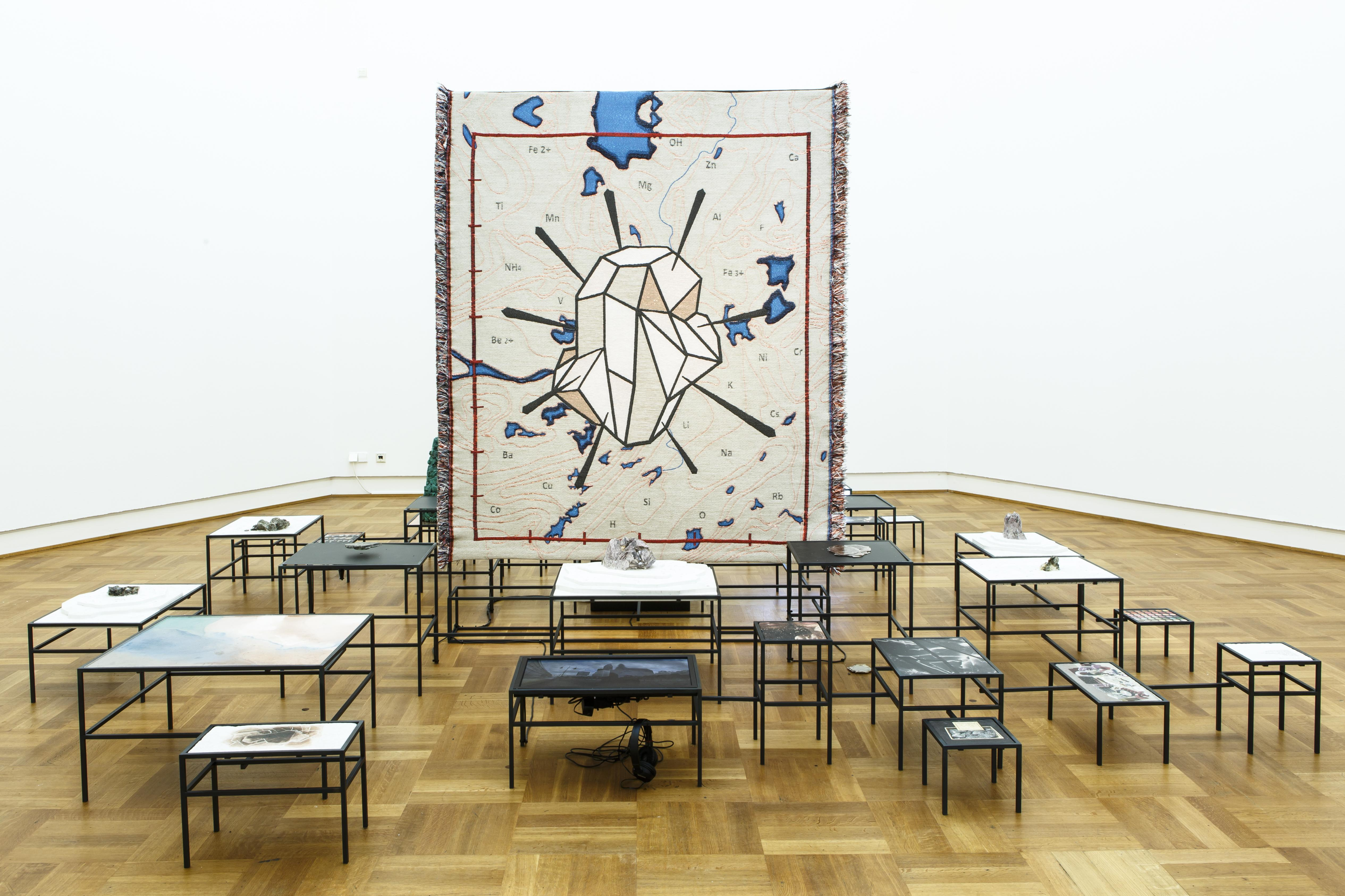 A large tapestry of a gem pierced by needles stands vertically in an art exhibition. It is surrounded by over a dozen metal tables of different sizes and heights.