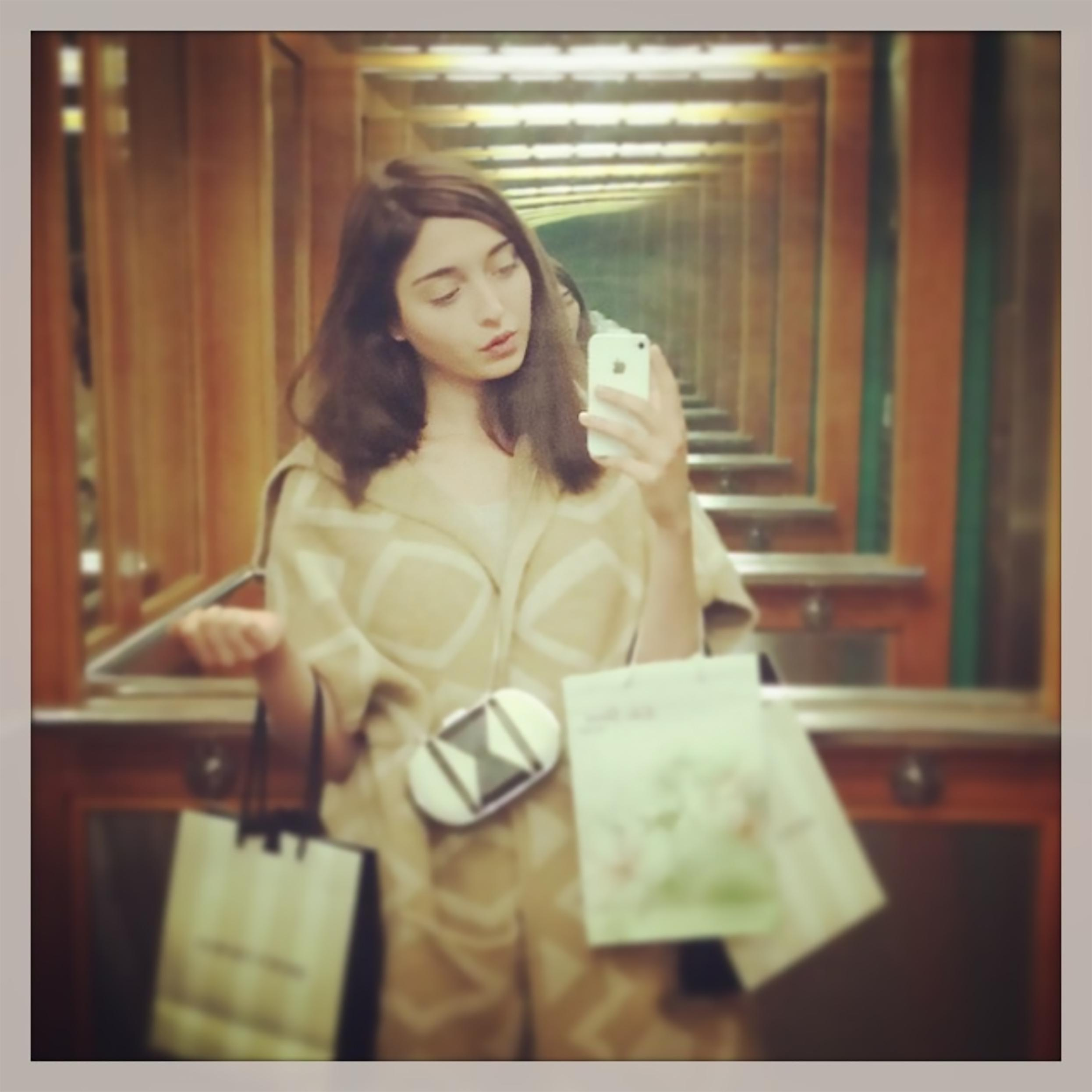 A brunette light-skinned woman takes a mirror selfie on her iPhone carrying shopping bags in the crooks of her arms.