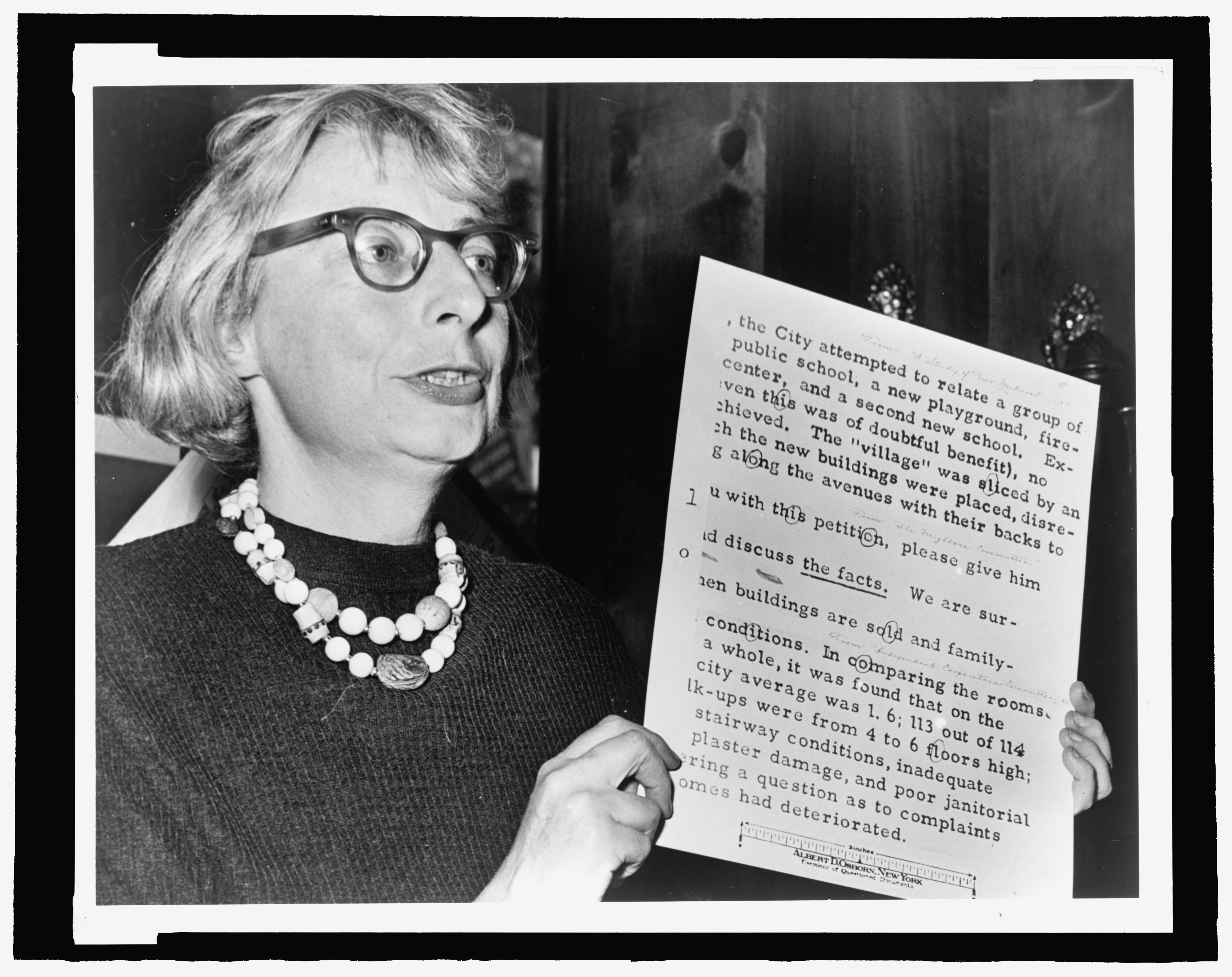 A black-and-white photograph shows a middle-aged, light-skinned woman holding a printed document aloft. It appears as though the woman is speaking.