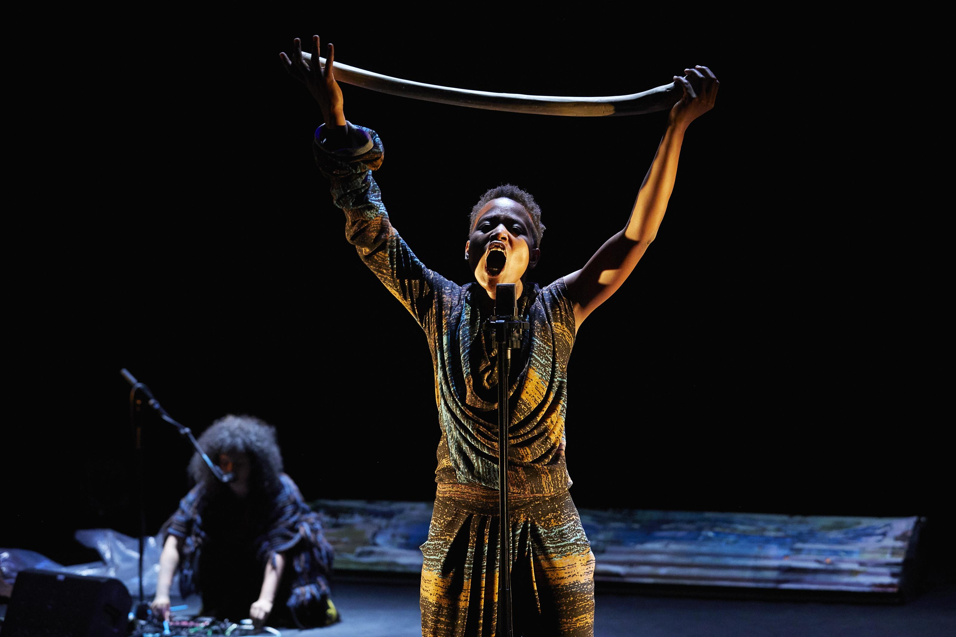 A young black woman stands at a microphone, her mouth open in a cry or in song. She holds a curved length of wood or bone above her head with both hands.