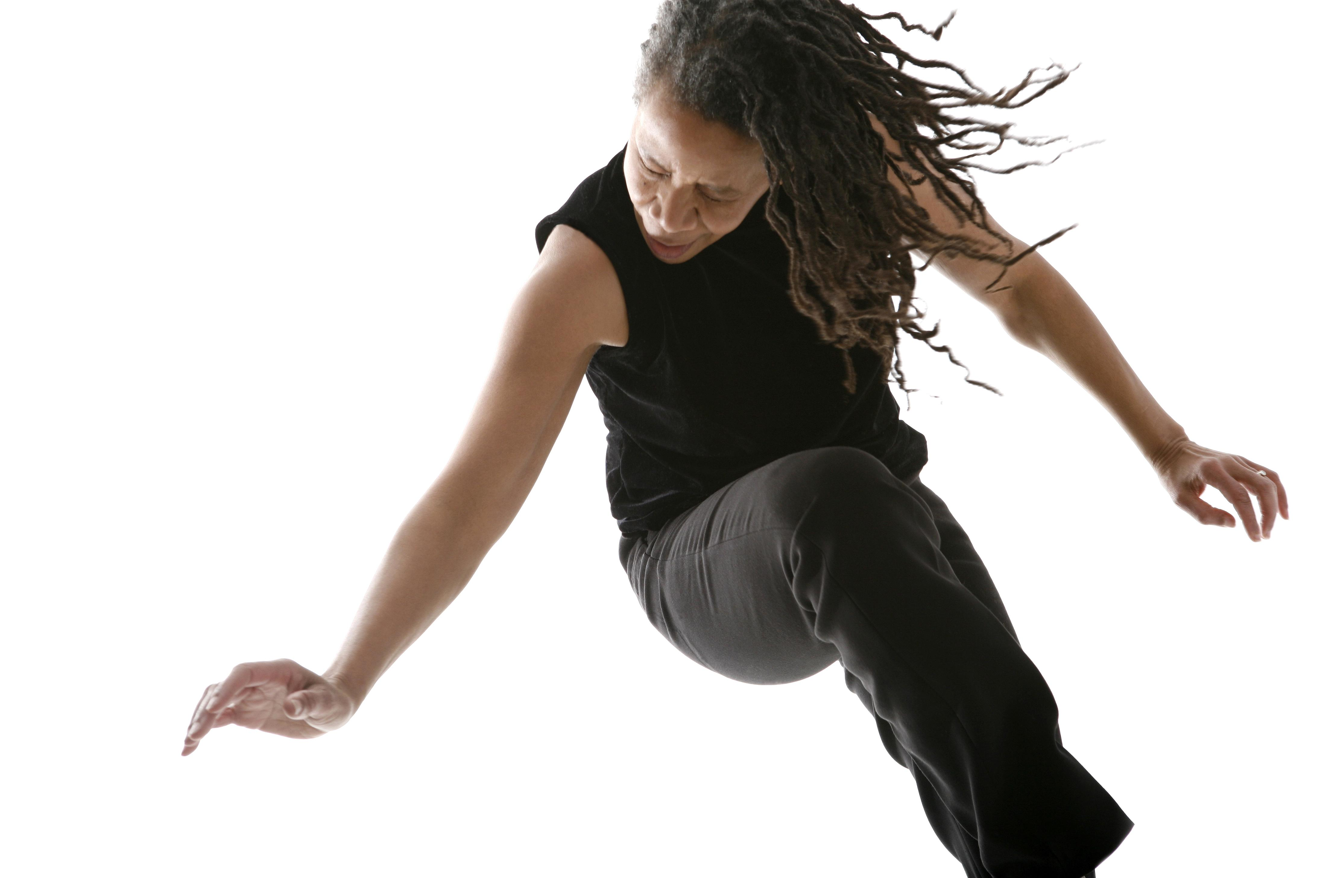 A woman pivots on her left leg, raising her right knee and ducking her head, her long dreadlocks swinging forward her as she turns.