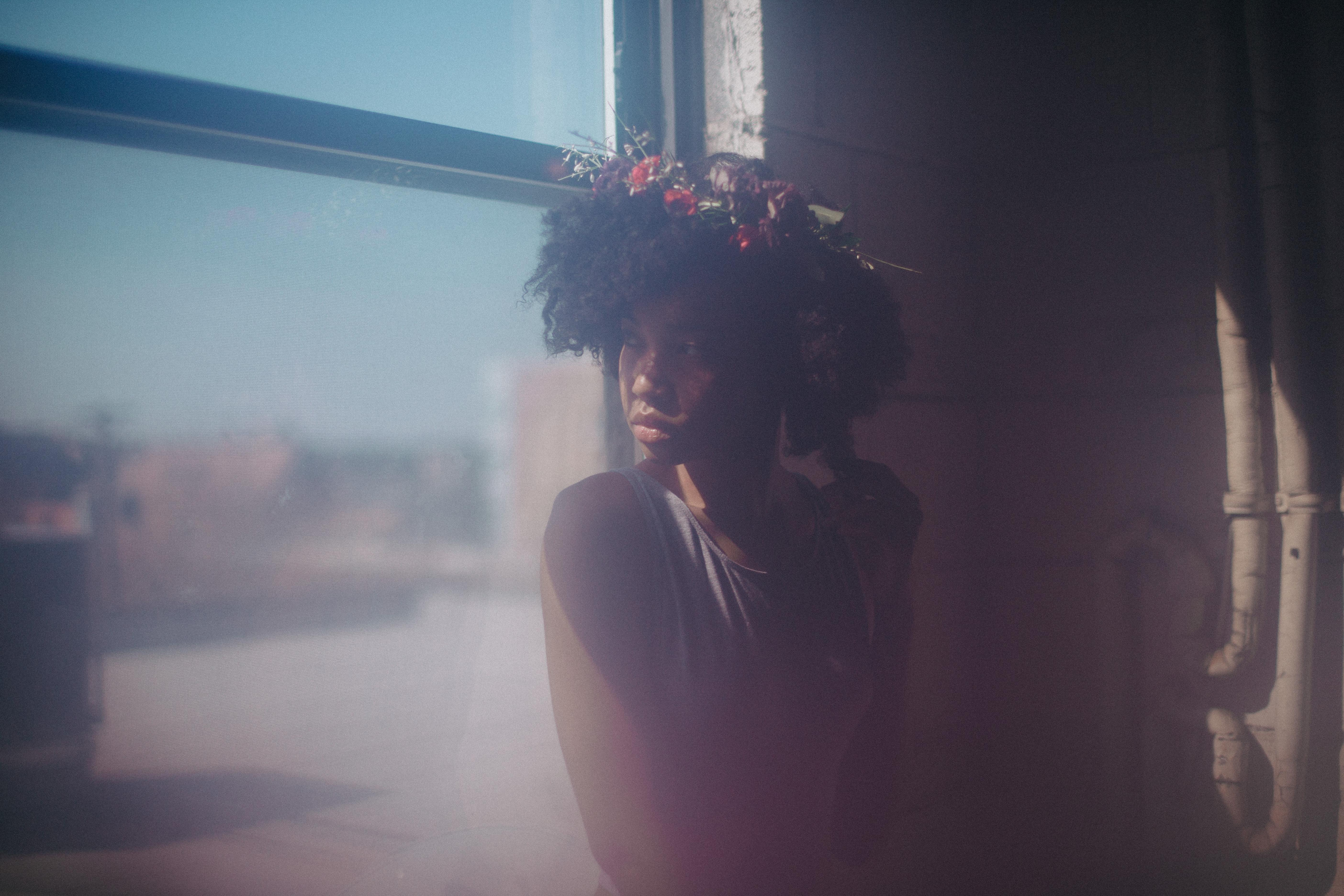 A young black woman, wearing a wreath of flowers in her hair and sitting in a window, turns to look over her shoulder. A misty haze slightly obscures the image.