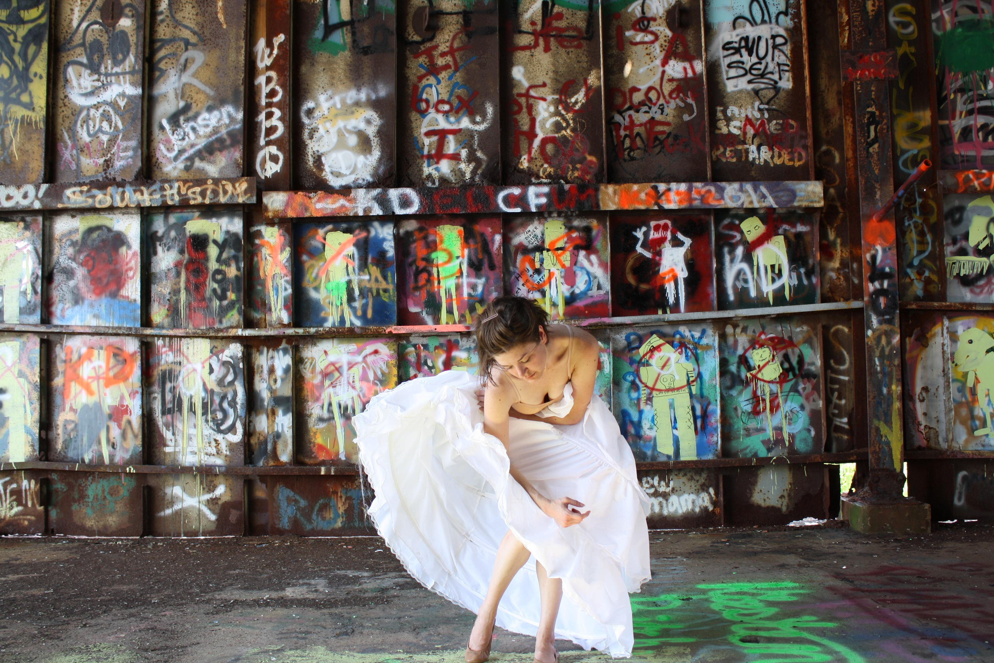 In an urban space filled with graffiti, a light-skinned brunette in a flowy white skirt gracefully bends her body forward in a dance-like motion.
