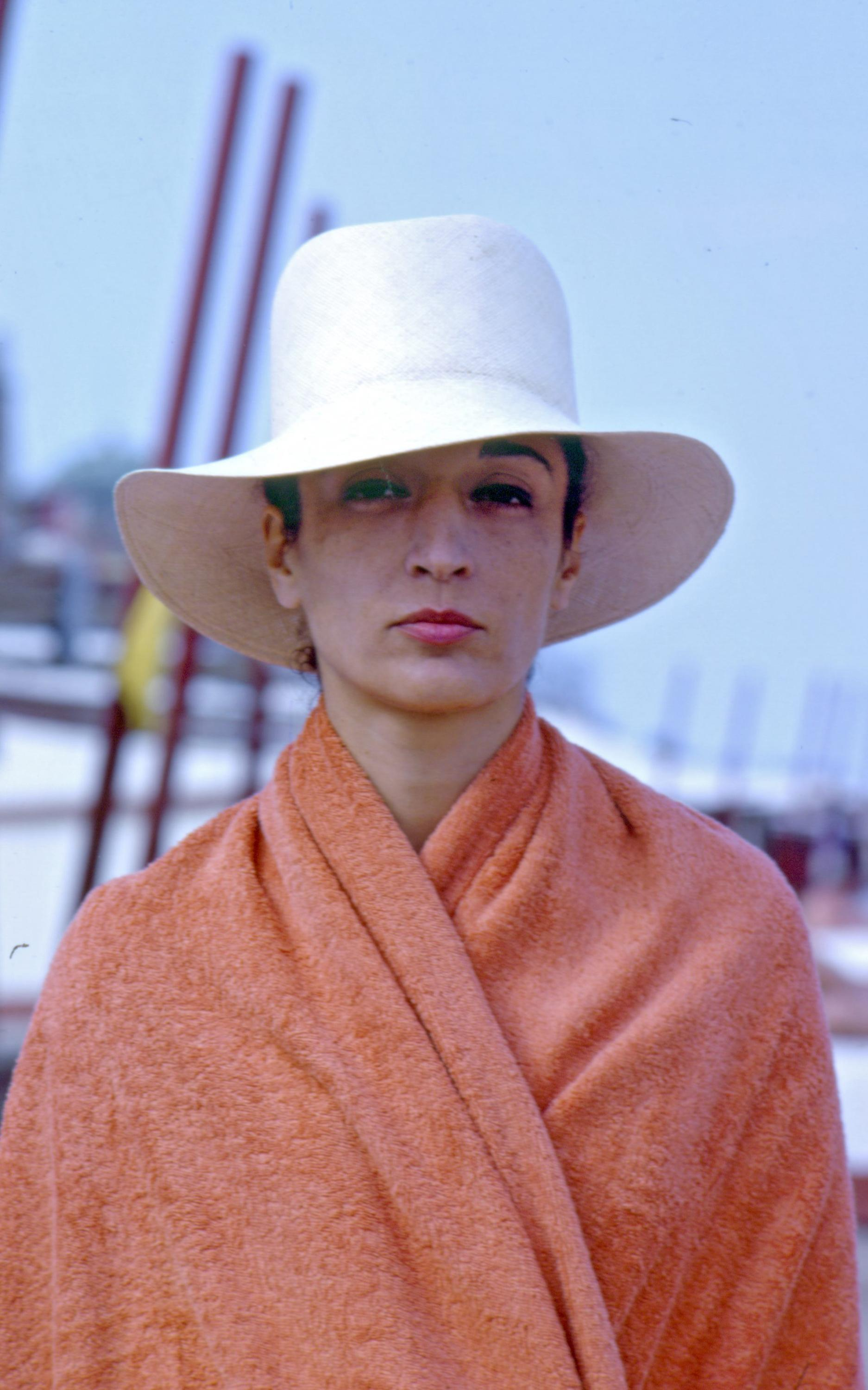 A portrait shows a light-skinned person wearing a large, wide-brimmed white hat and an orange shawl or blanket.