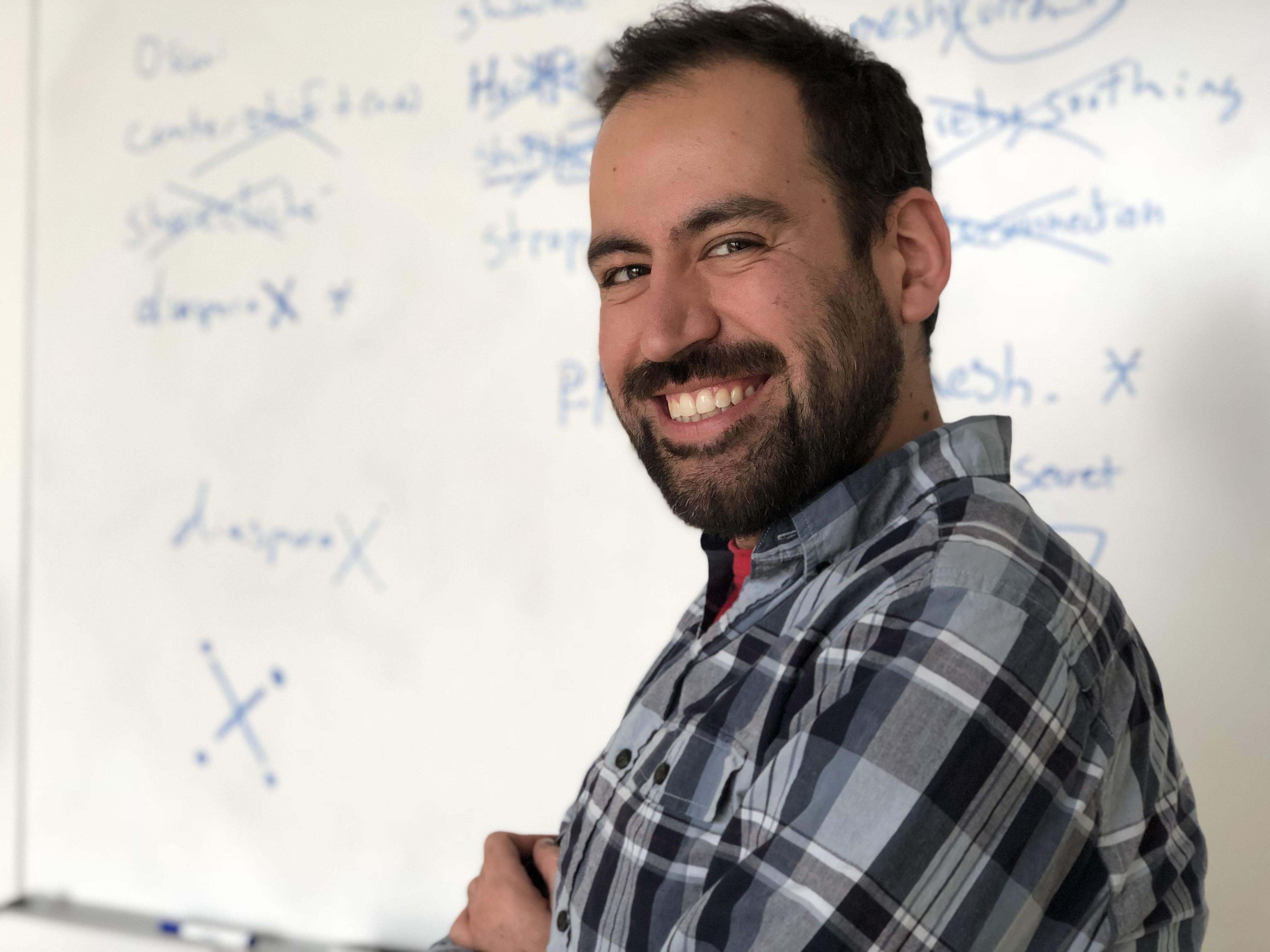 A man in a plaid shirt crosses his arms and faces the viewer. He stands in front of a whiteboard with lists of words, some crossed out.