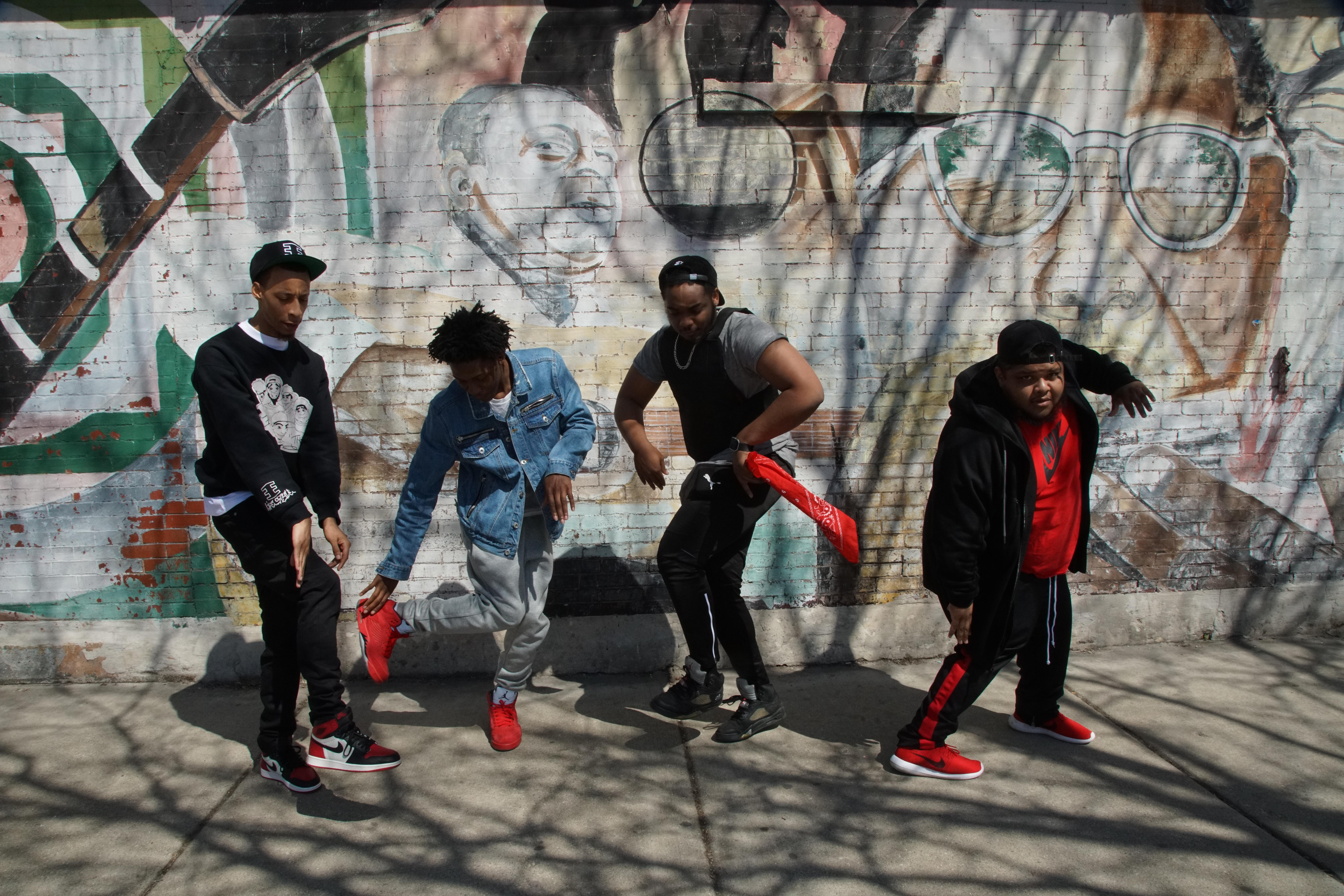 Four young men dance on a city sidewalk in front of a mural on a brick wall.