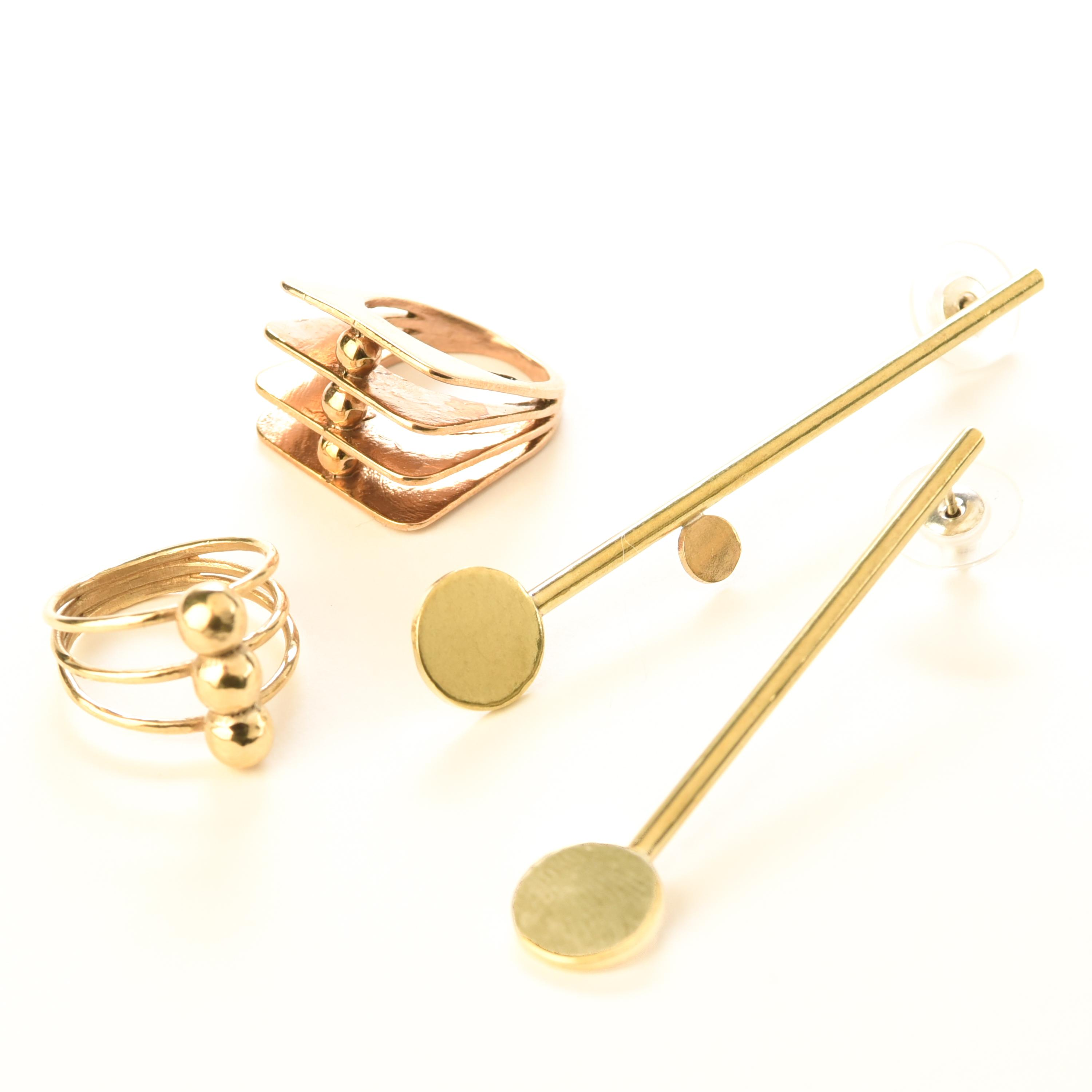 Two unique rings and a pair of earrings share a motif of gold circles and lines.