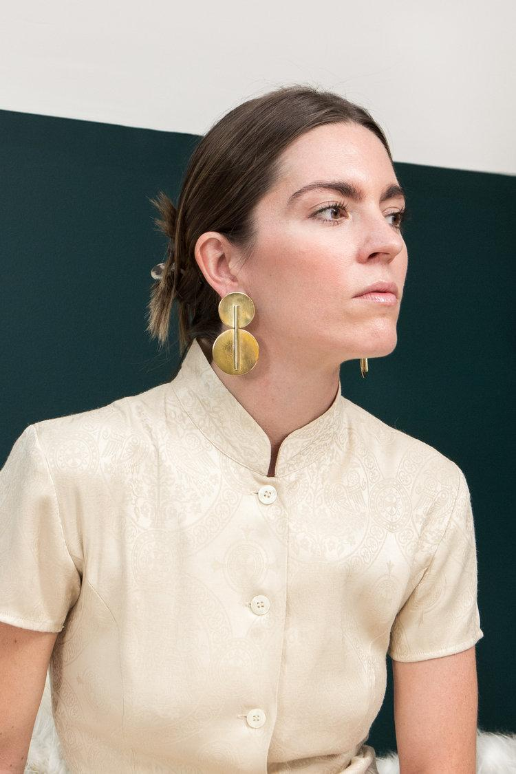A light-skinned person models a pair of large gold, geometric statement earrings.