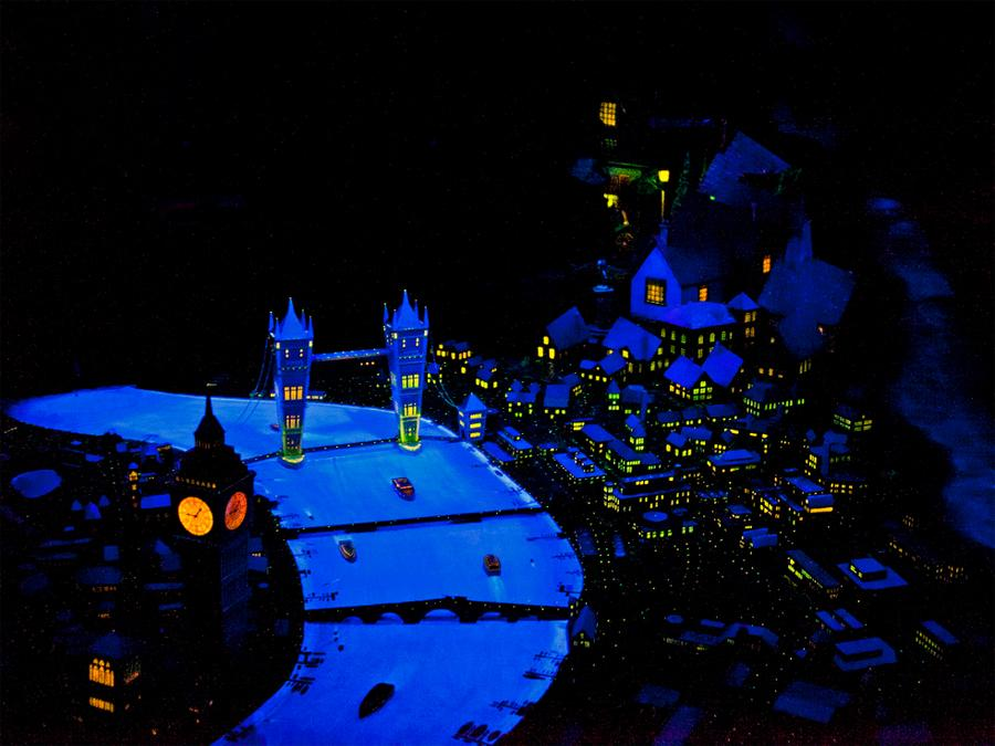 A model reproduction of a cityscape at night is intersected by a river which glows with blue light alongside the warm glowing windows of urban buildings.