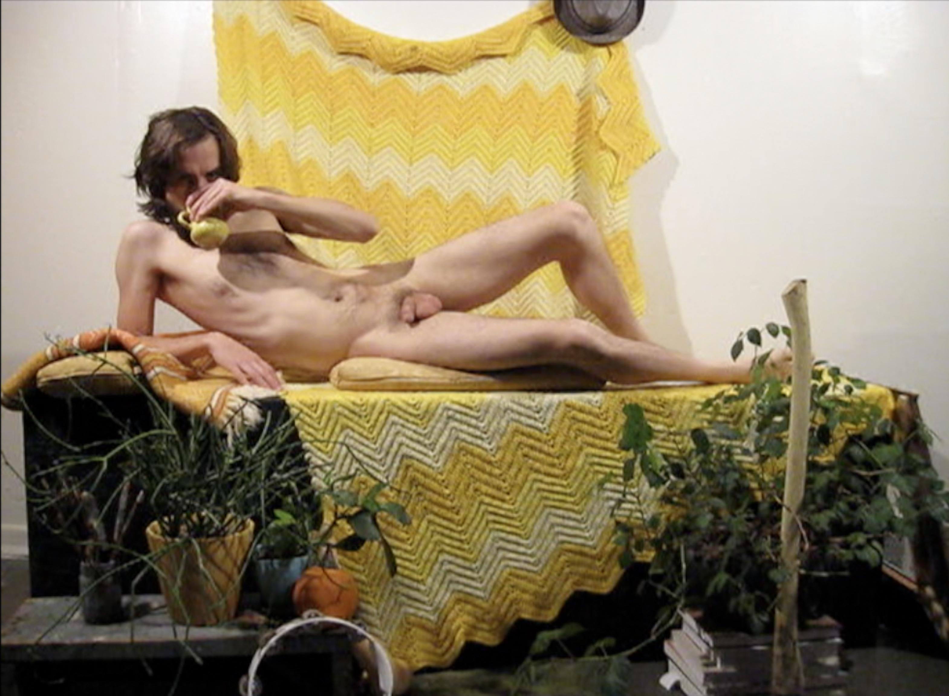 A nude masculine person lounges on a platform covered in yellow blankets and surrounded by potted plants. They drink from a yellow mug, as if posing for a figure drawing session.