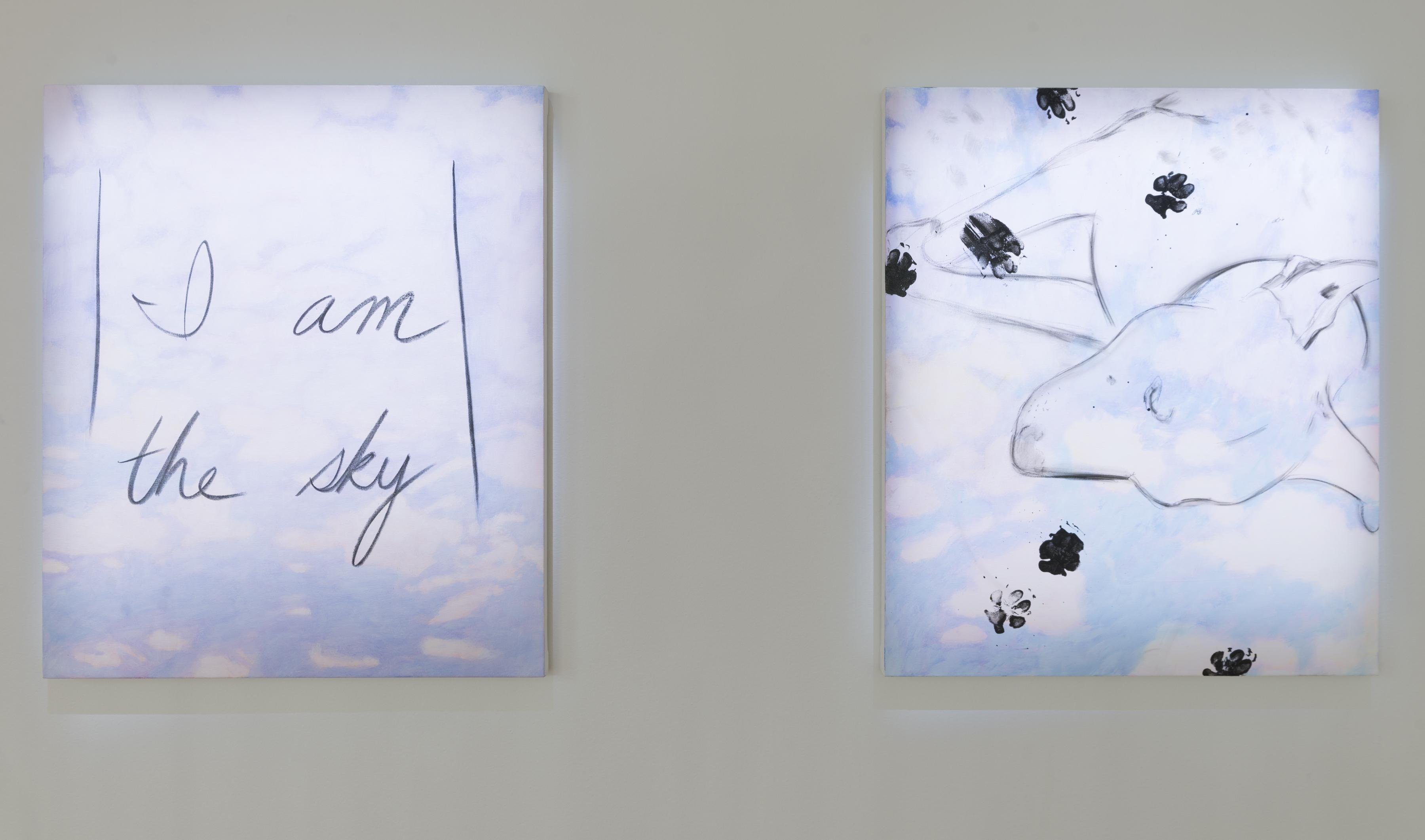 """Two paintings of idyllic cloudy blue skies hang side by side. One reads """"I am the sky"""" and the other outlines a sleeping dog overlapped with inky paw prints."""
